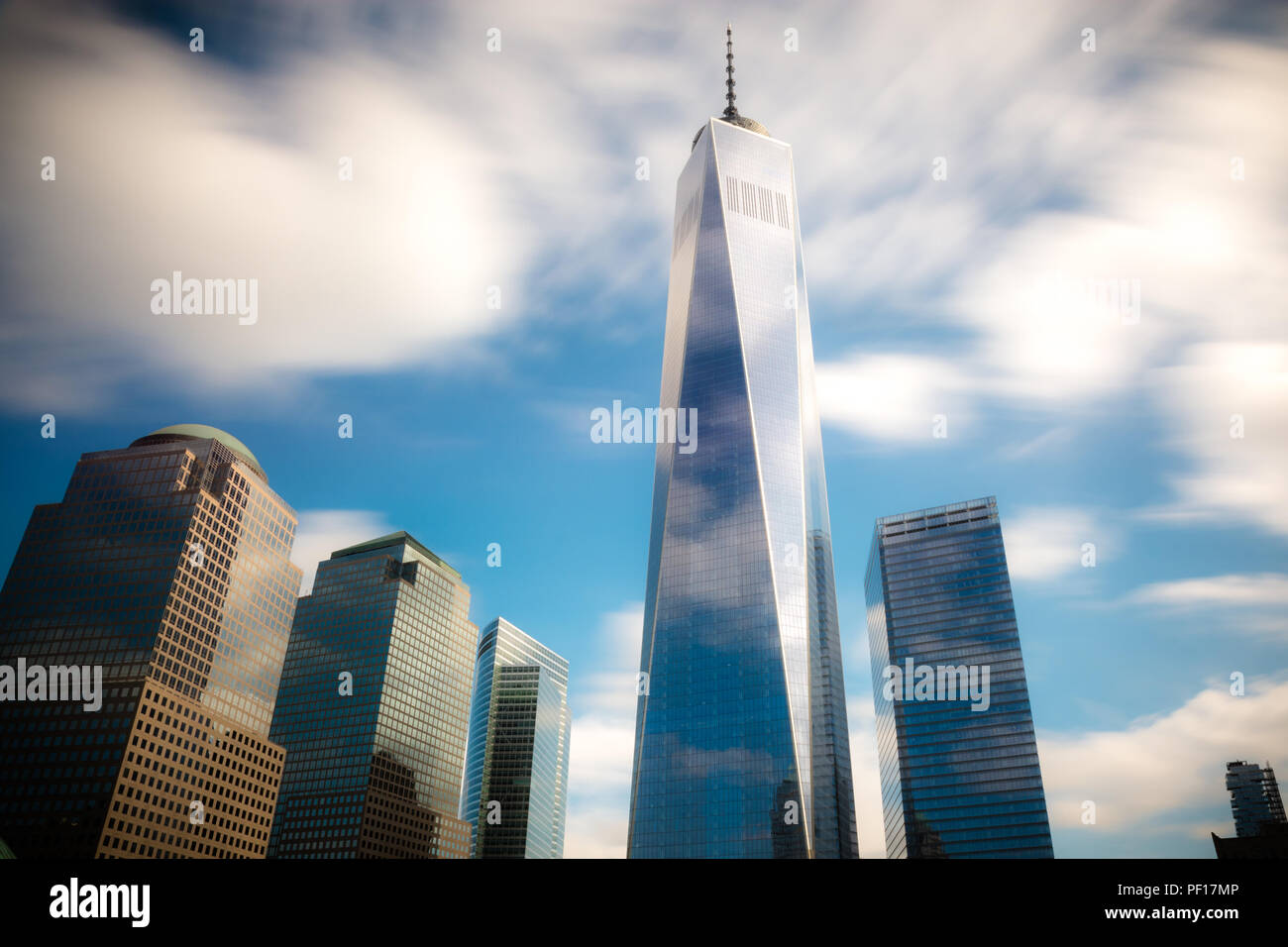 Fast moving clouds over One WTC and the 9/11 memorial in Lower Manhattan, New York City. - Stock Image