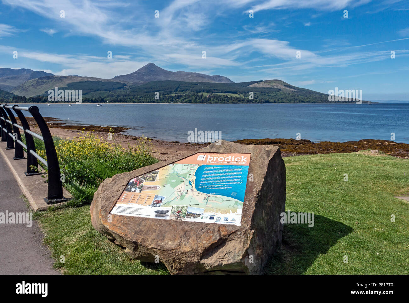 Stone with interpretation panel inserted at the beach at Brodick Isle of Arran North Ayrshire Scotland UK with Goat Fell across Brodick Bay - Stock Image