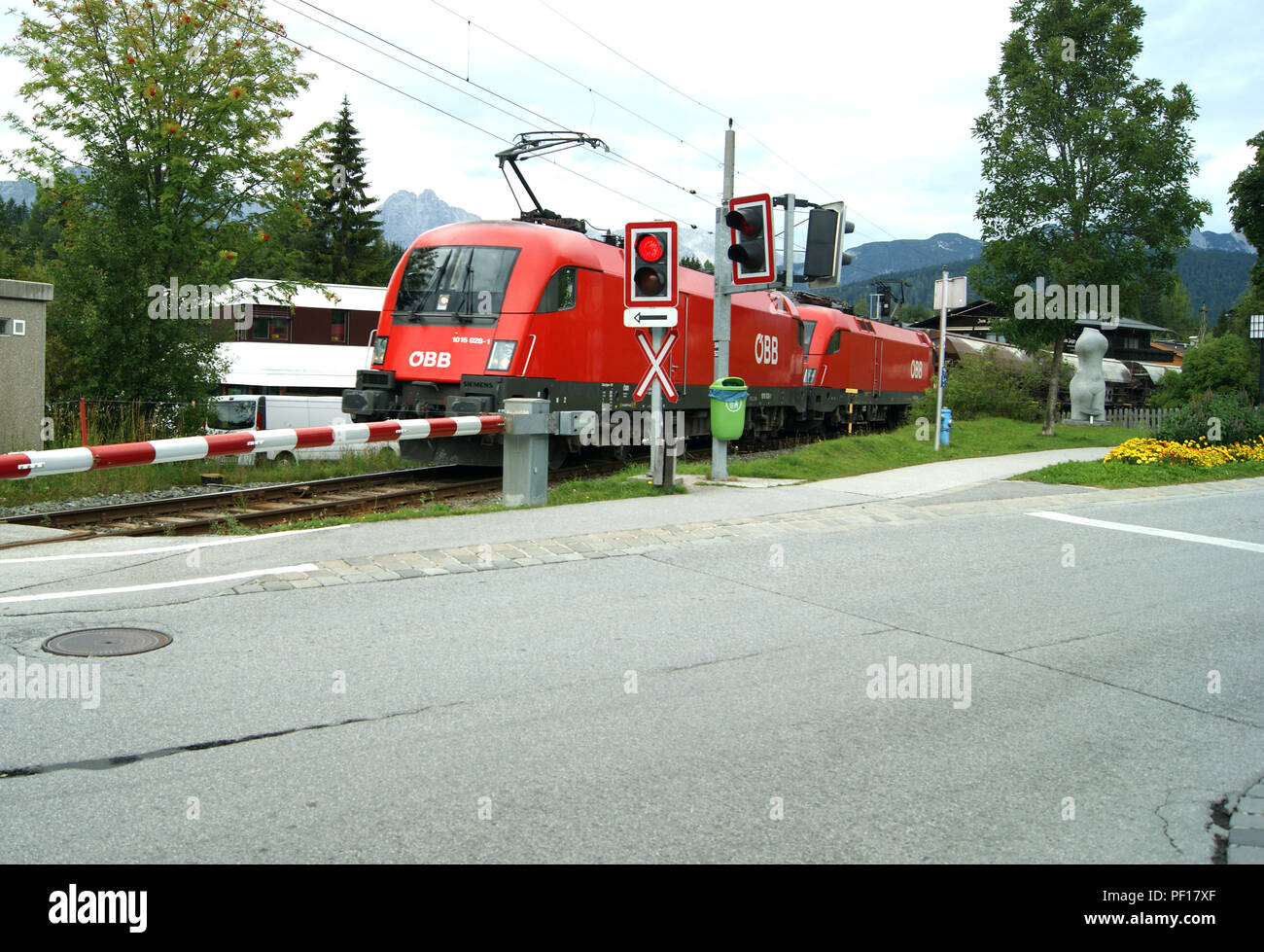 OBB 1016-028-1 locomotive leads another of her class across a level crossing at Seefeld with a freight trailn - Stock Image