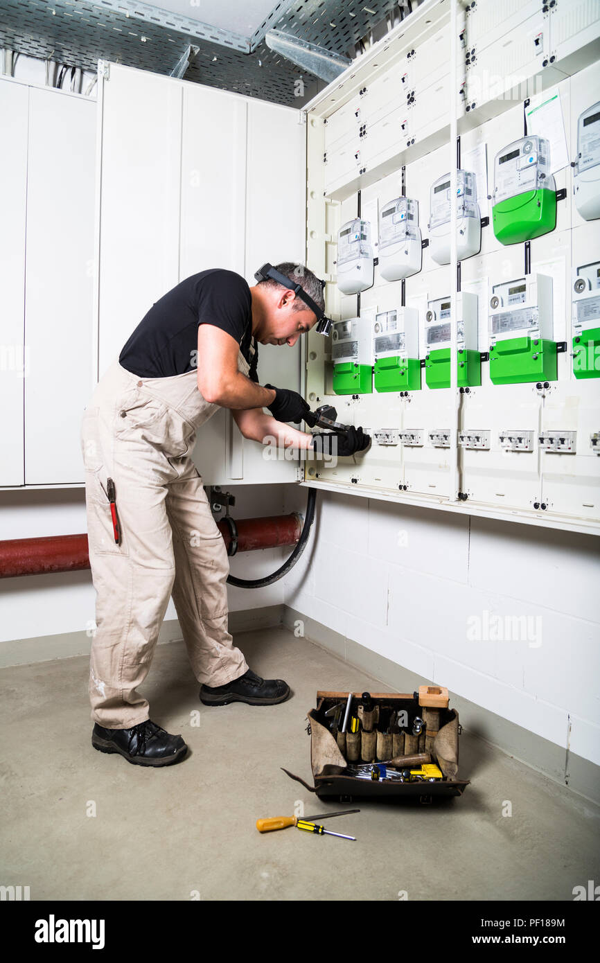 Electrician with box of tools testing fuse box or switch box by measuring device - Stock Image