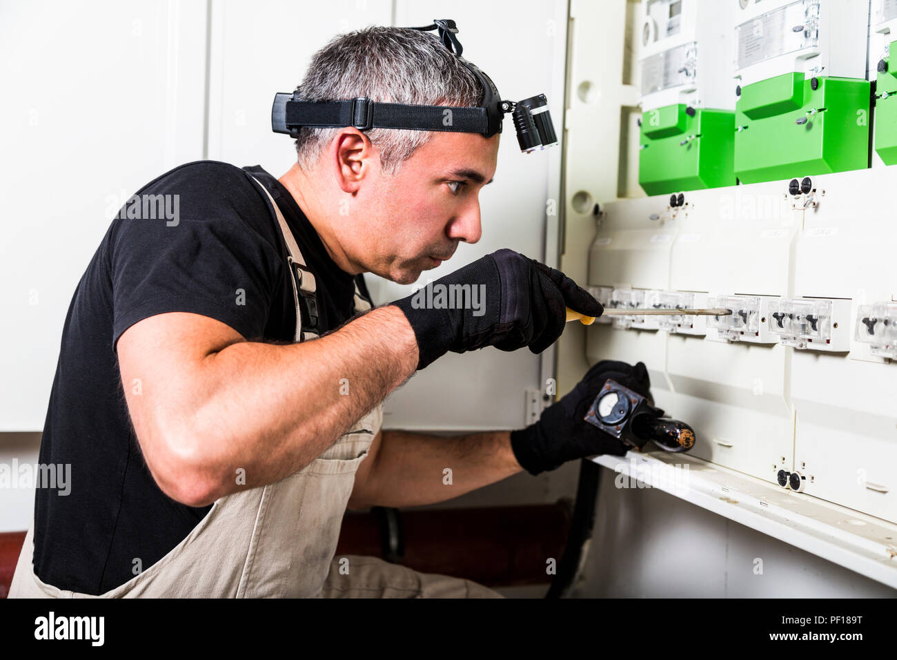 Electrician repairs and measures fuse box or switch box - Stock Image