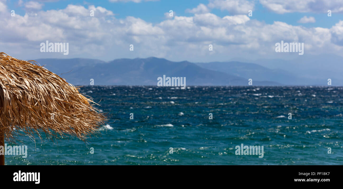 Straw umbrella closeup, windy beach and stormy sea and sky background - Stock Image