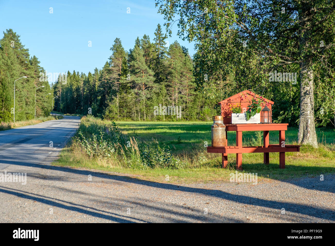 Traditional milk churn stand maintained for decorative purposes along a road in northern Sweden - Stock Image