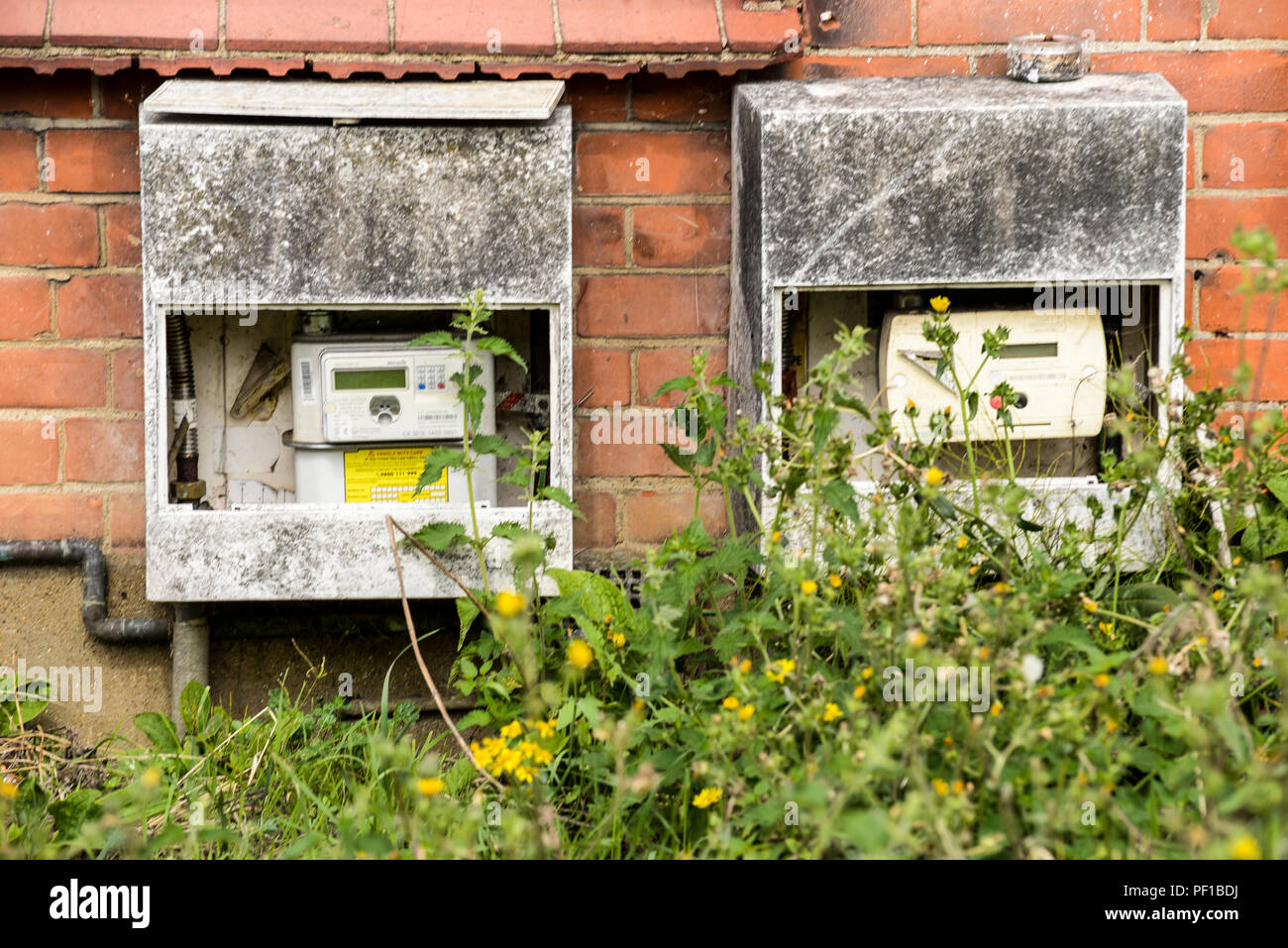 Damaged and decrepit gas and electric meters. Overgrown garden. Weeds. House. Property - Stock Image