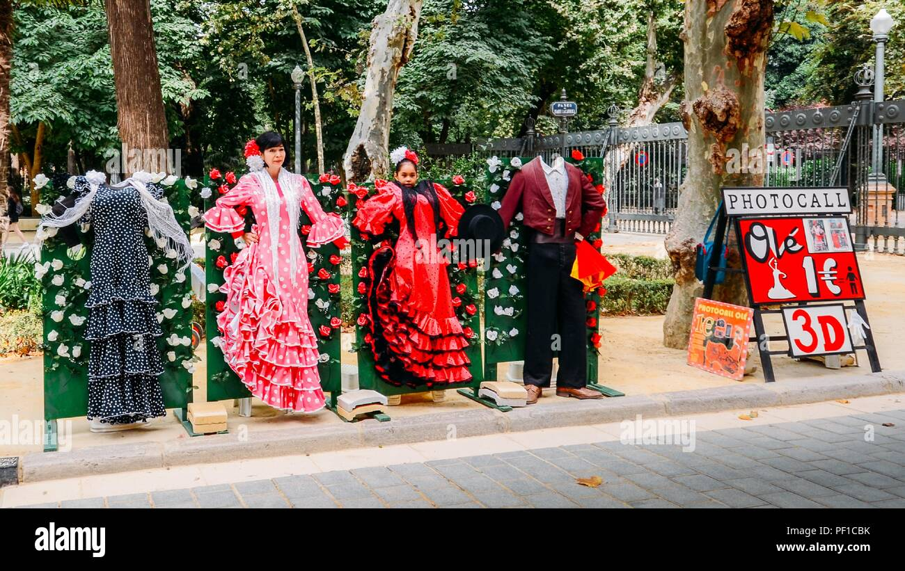 Seville, Spain - July 15, 2018: Photo opportunity for tourists to dress in typical Seville Flamenco dresses, near Plaza Espana - Stock Image
