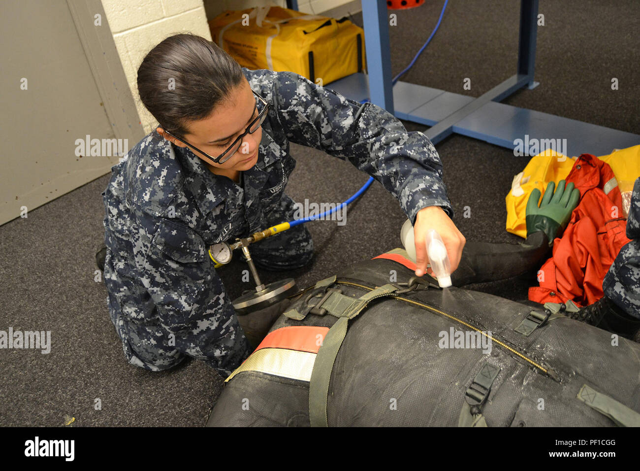 160127-N-BO364-005  JACKSONVILLE, Fla. (Jan. 27, 2016) Aircrew Survival Equipmentman Airman Apprentice Jazmin Velez sprays liquid onto an inflated CWU-60 dry suit to check for leaks. The suit is used by P-3C Orion crewmembers who have to enter a cold-water environment. (U.S. Navy Photo by Clifford Davis/Released) - Stock Image