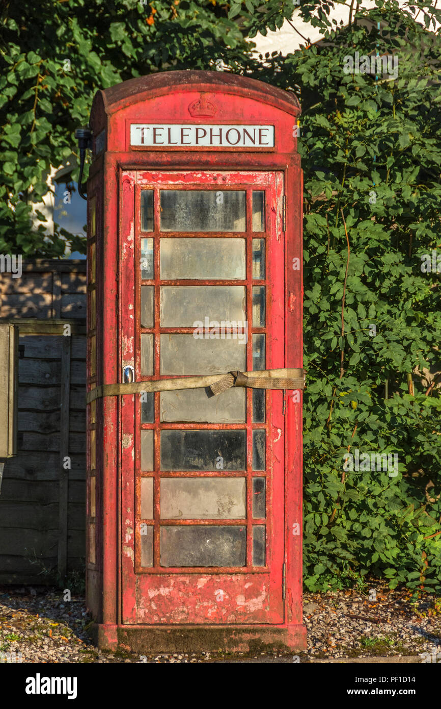 The red telephone box, a telephone kiosk for a public telephone designed by Sir Giles Gilbert Scott. derelict and in poor condition - Stock Image