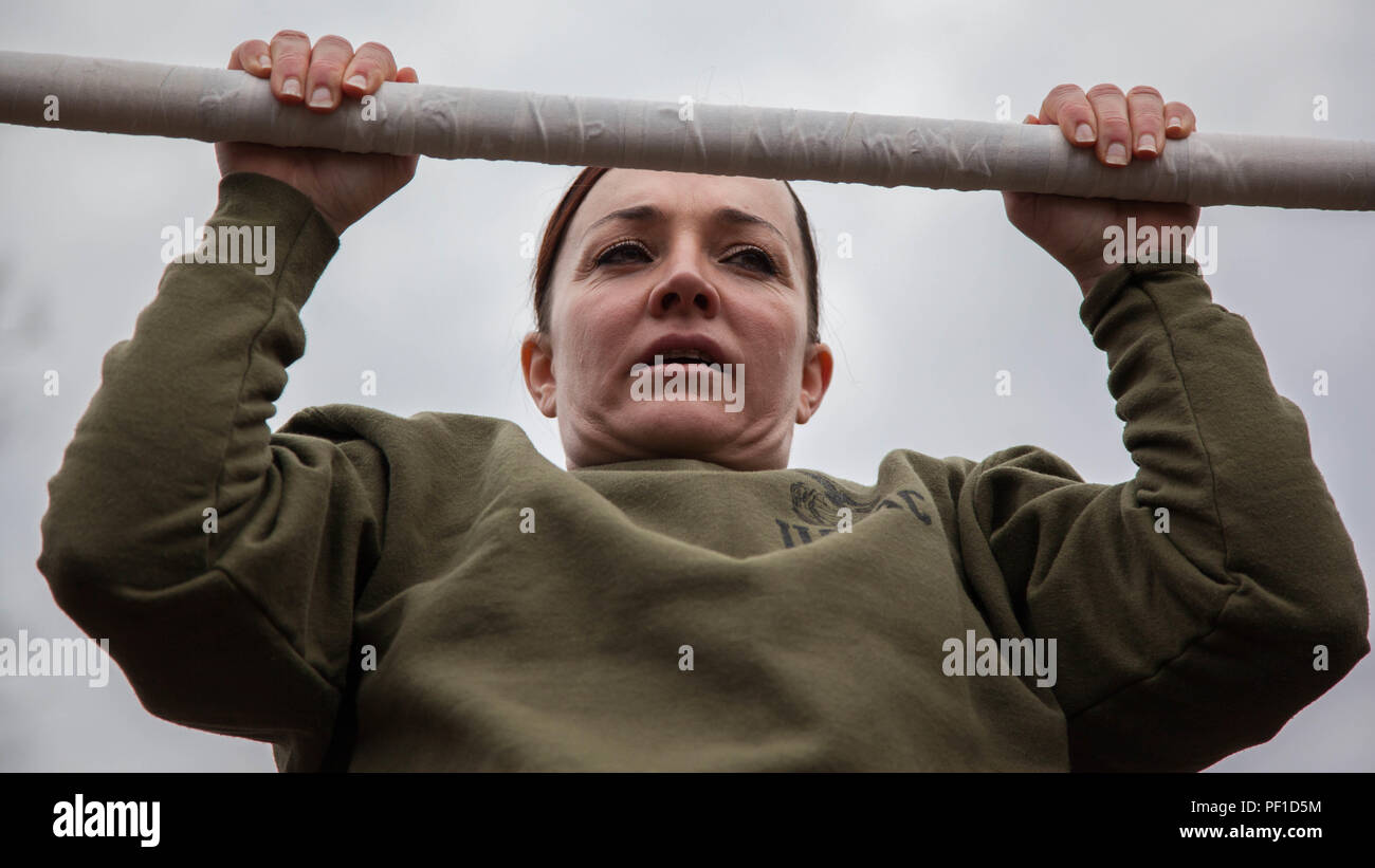 Major Misty Posey demonstrates proper form for pull-ups to Marines at Marine Corps Base Quantico, Virginia, Feb. 19, 2016. Posey, a plans officer for Manpower Integration, developed a pull-up program to assist Marines with their pull-ups and proper form. - Stock Image
