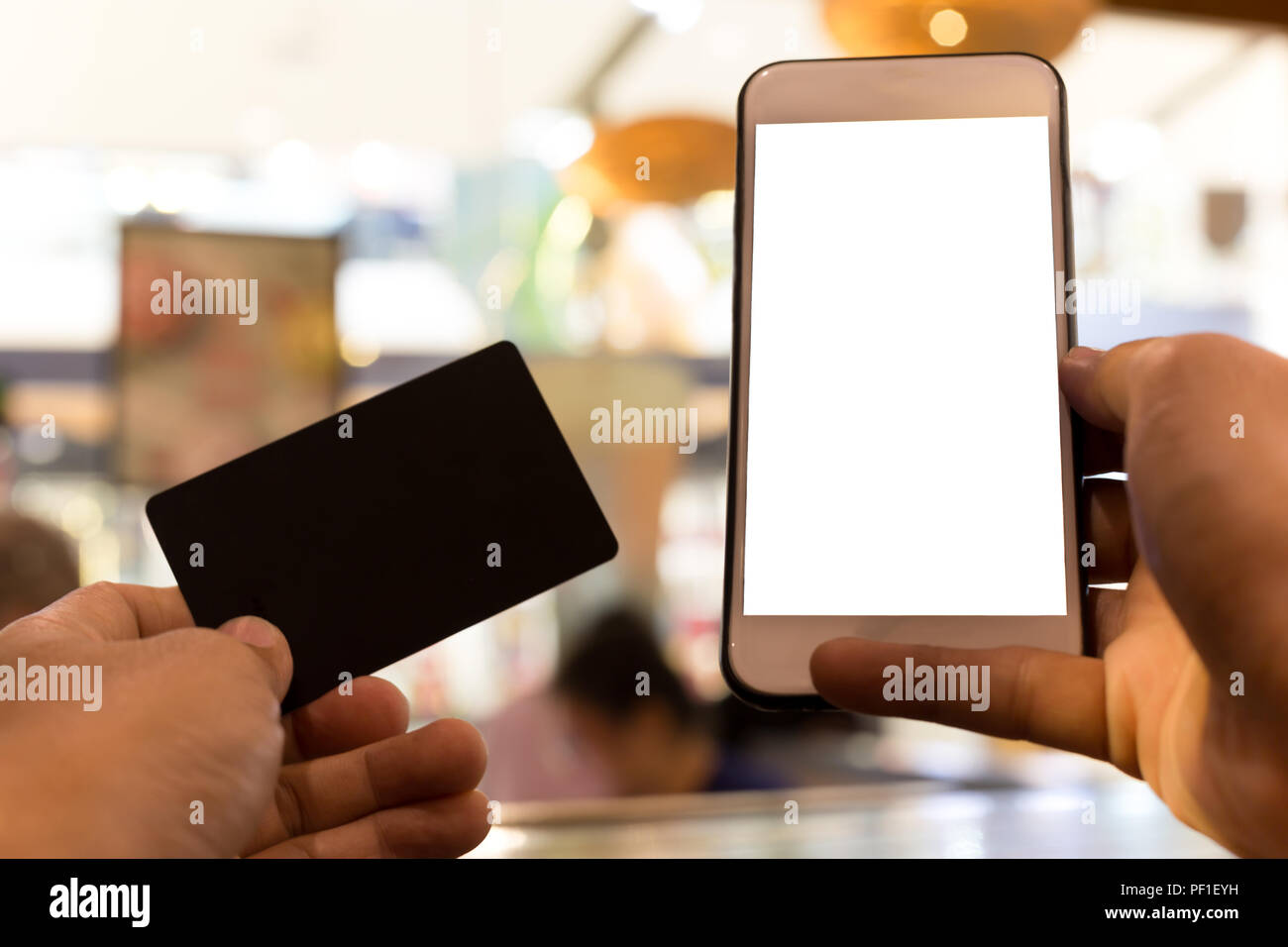 Hands holding credit card and using cell phone  - Stock Image