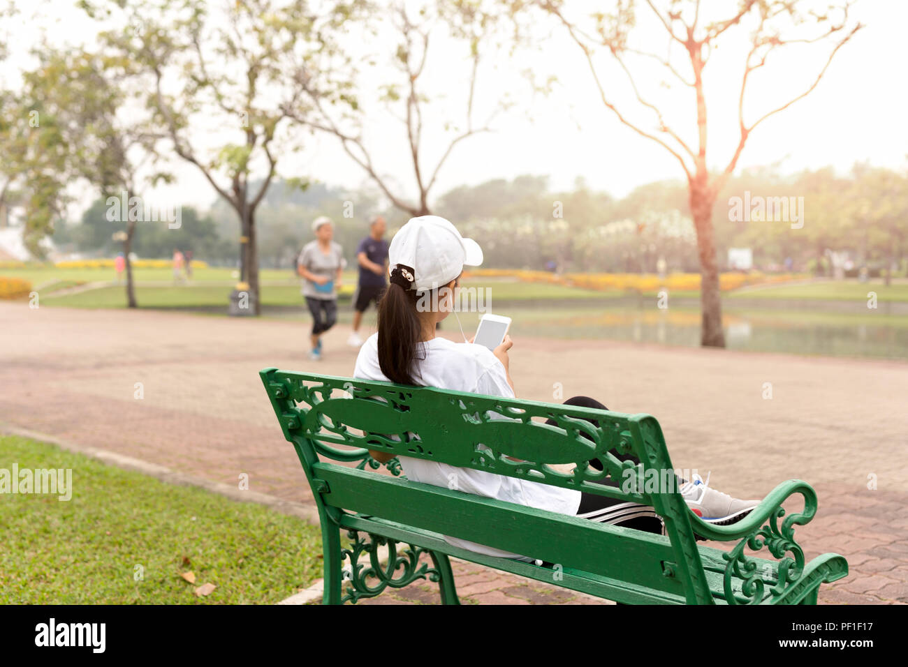 Woman sit on a bench relaxing using cell phone - Stock Image
