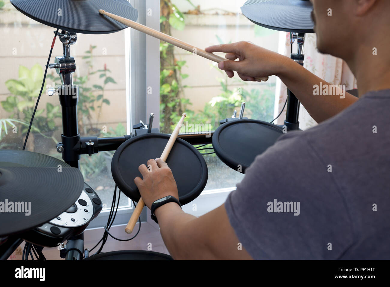 Man's rehearsal playing electronic drums - Stock Image