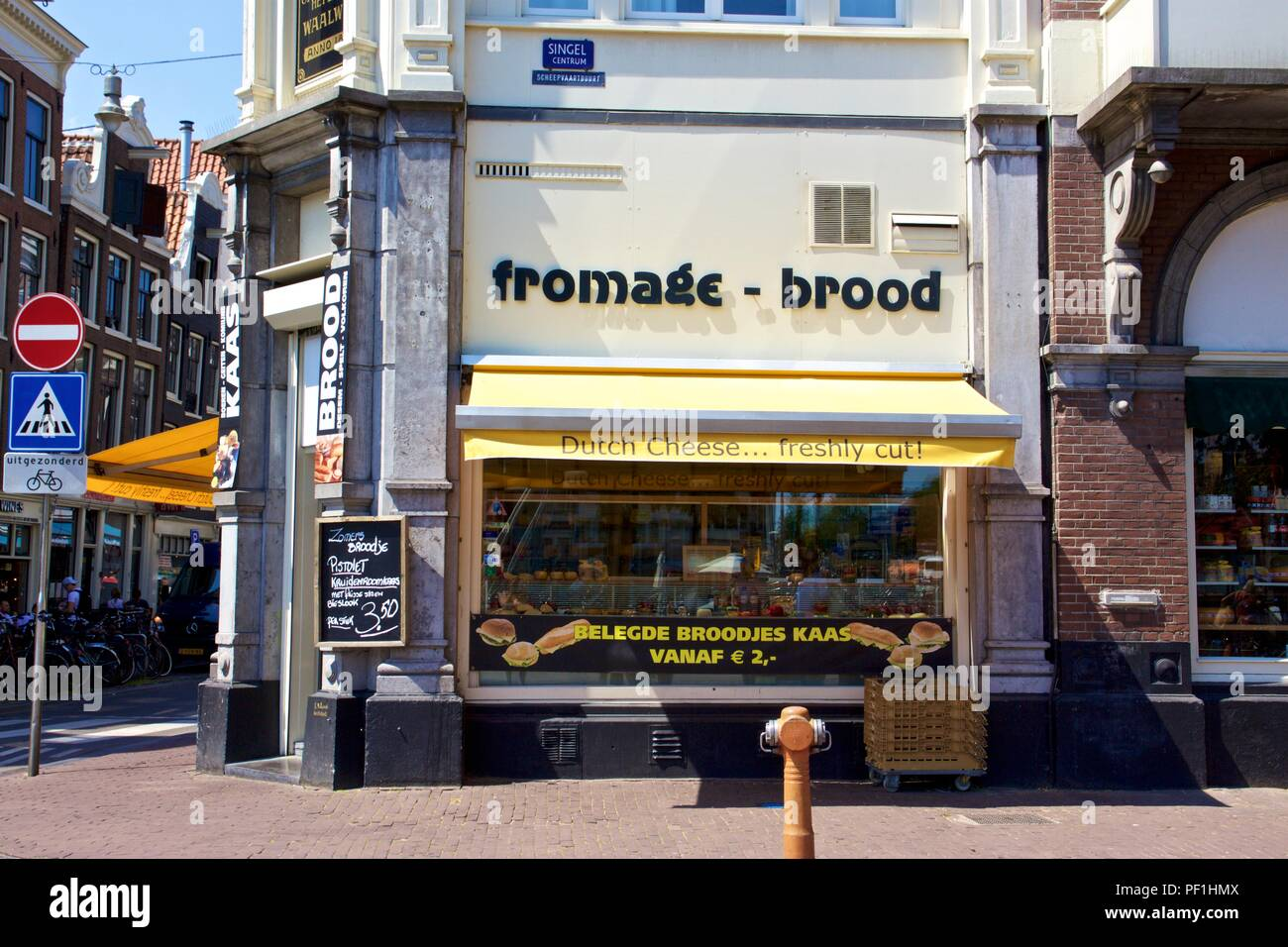 A Dutch Cheese shop with a yellow shopfront advertising 'fromage - brood' on Singel, Amsterdam, the Netherlands - Stock Image