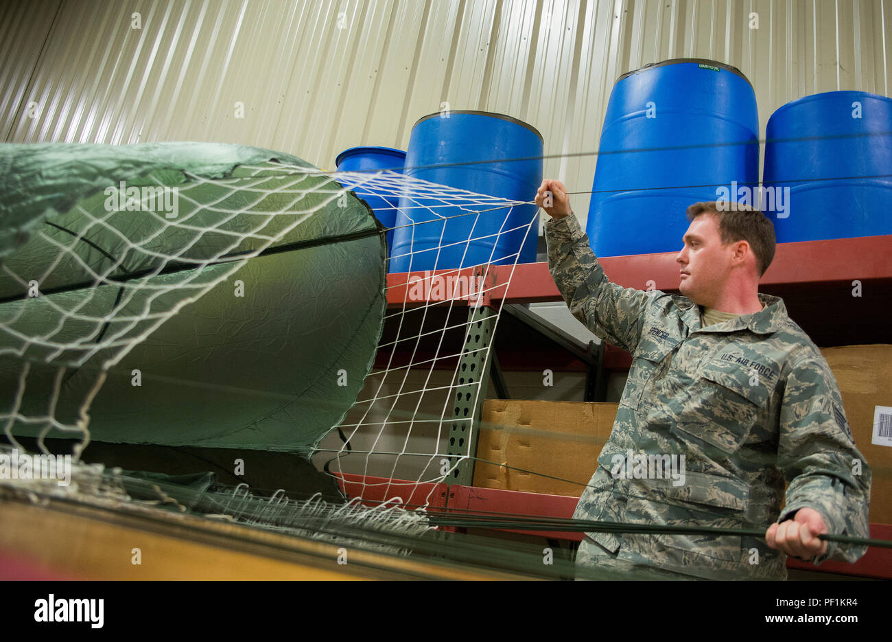 Staff Sgt. Justin Spencer, 919th Special Operations Logistics Readiness Squadron, sets up a parachute at Duke Field, Fla.  The parachutes are attached to 300-pound bundles and loaded onto aircraft so new loadmasters can perform their initial airdrop training and prior-qualified Airmen can maintain proficiency.  (U.S. Air Force photo/Sam King) - Stock Image