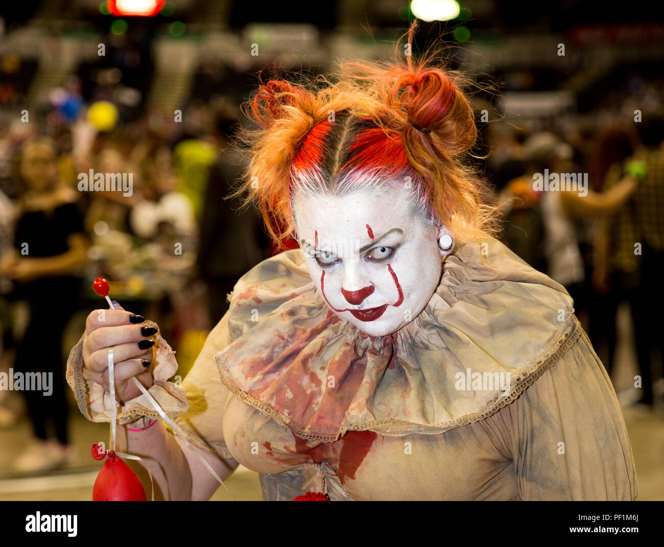 A female cosplayer dressed as Pennywise the clown from Stephen King's November IT and looking evil and menacing at a comic con event - Stock Image