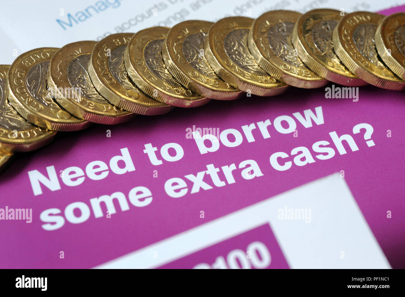 LOAN LEAFLETS WITH ONE POUND COINS RE BORROWING SHORT TERM LOANS PAYDAY APR EXTRA CASH UK - Stock Image