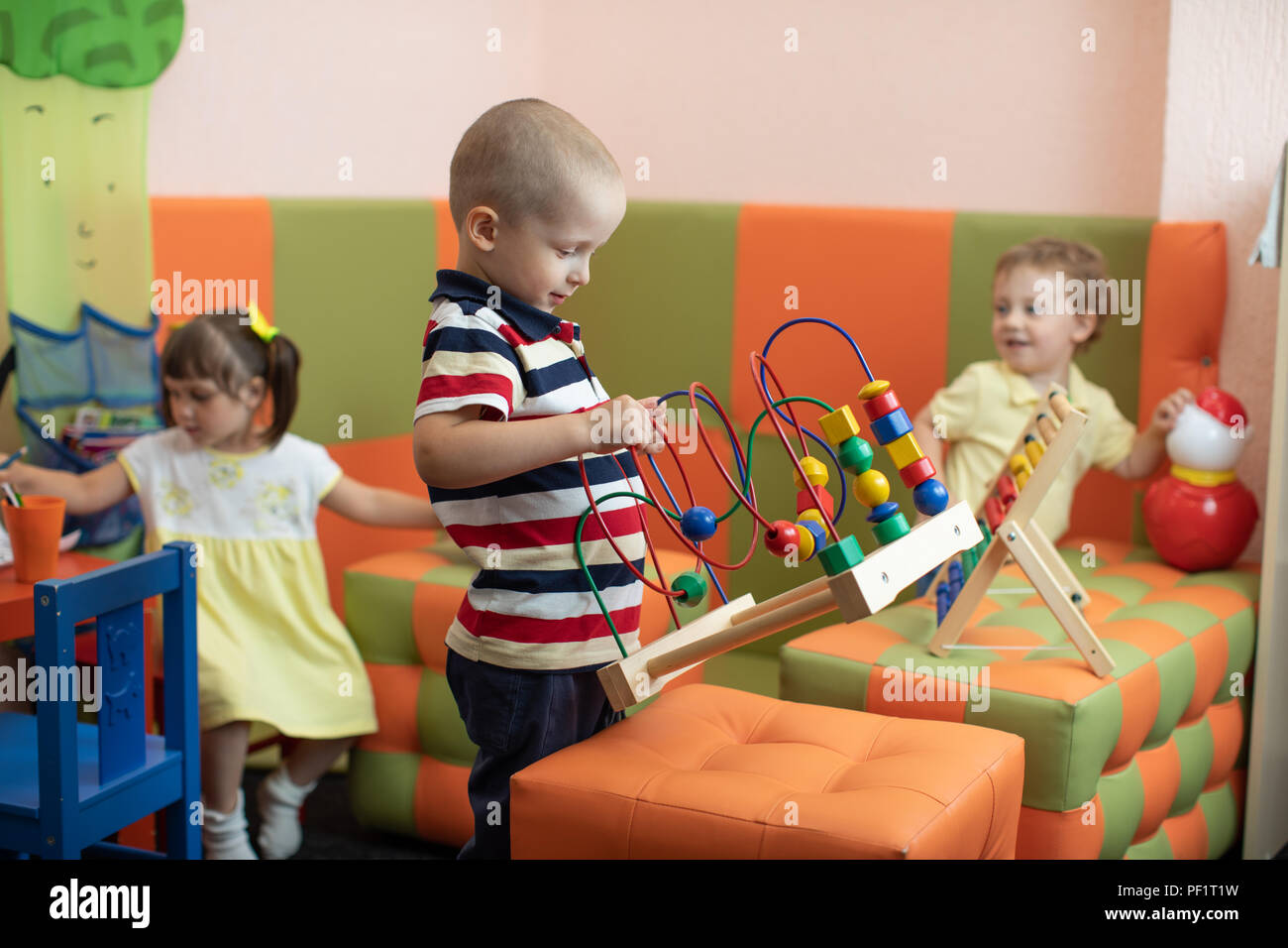 Group of children playing in kindergarten or daycare centre - Stock Image
