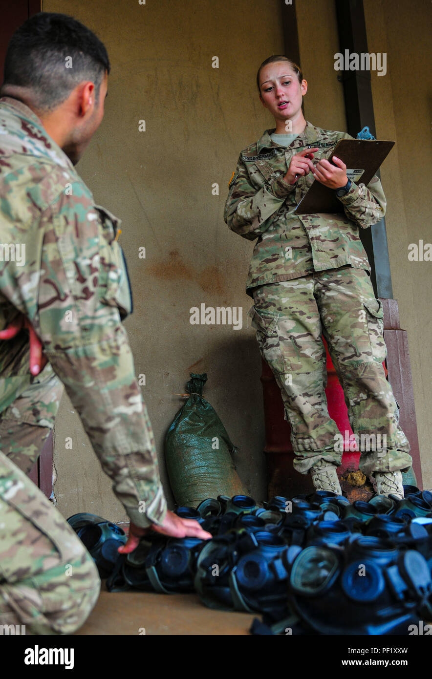 During an inventory check on Feb. 17, 2016, on Schofield Barracks, here, 1st Lt. Brenna Heisterman, an engineering officer and the executive officer with Headquarters and Headquarters Company, 2nd Brigade Combat Team, 25th Infantry Division, and Sgt. Macel Gonzalez, an infantryman with HHC, 2nd BCT, discuss the amount protective masks assigned to HHC. Heisterman had recently returned from San Diego, where she donated her bone marrow to a cancer patient from the country of Turkey. (U.S. Army photo by Sgt. Ian Ives, 2nd Stryker Brigade Combat Team Public Affairs/Released) - Stock Image