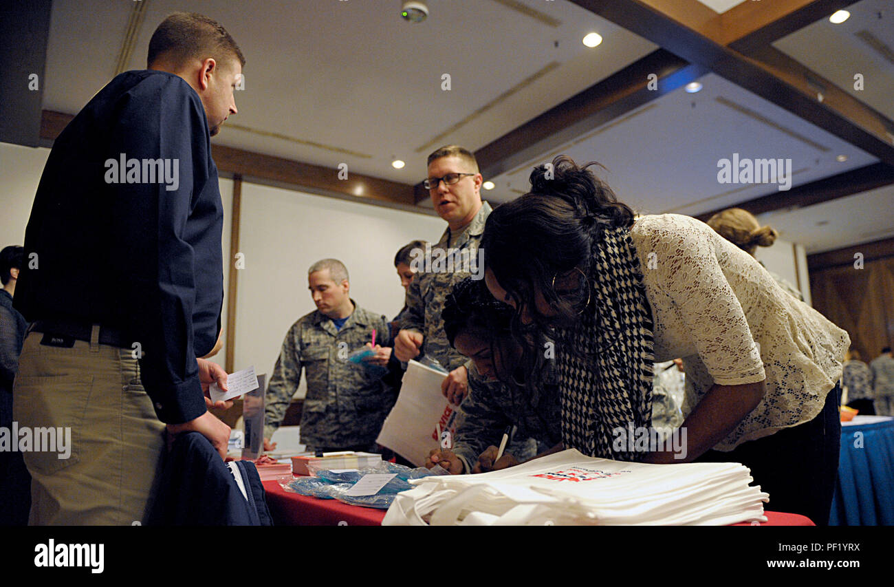 """Members of the Kaiserslautern Military Community talk to a Service Credit Union representative during the Military Saves Week kickoff Feb. 19, 2016, at Ramstein Air Base, Germany. During the event, KMC members were able to learn about and sign up for saving plans through several financial institutions. The theme for the 2016 Military Saves Week is """"Make Saving Automatic."""" (U.S. Air Force photo/Staff Sgt. Timothy Moore) - Stock Image"""