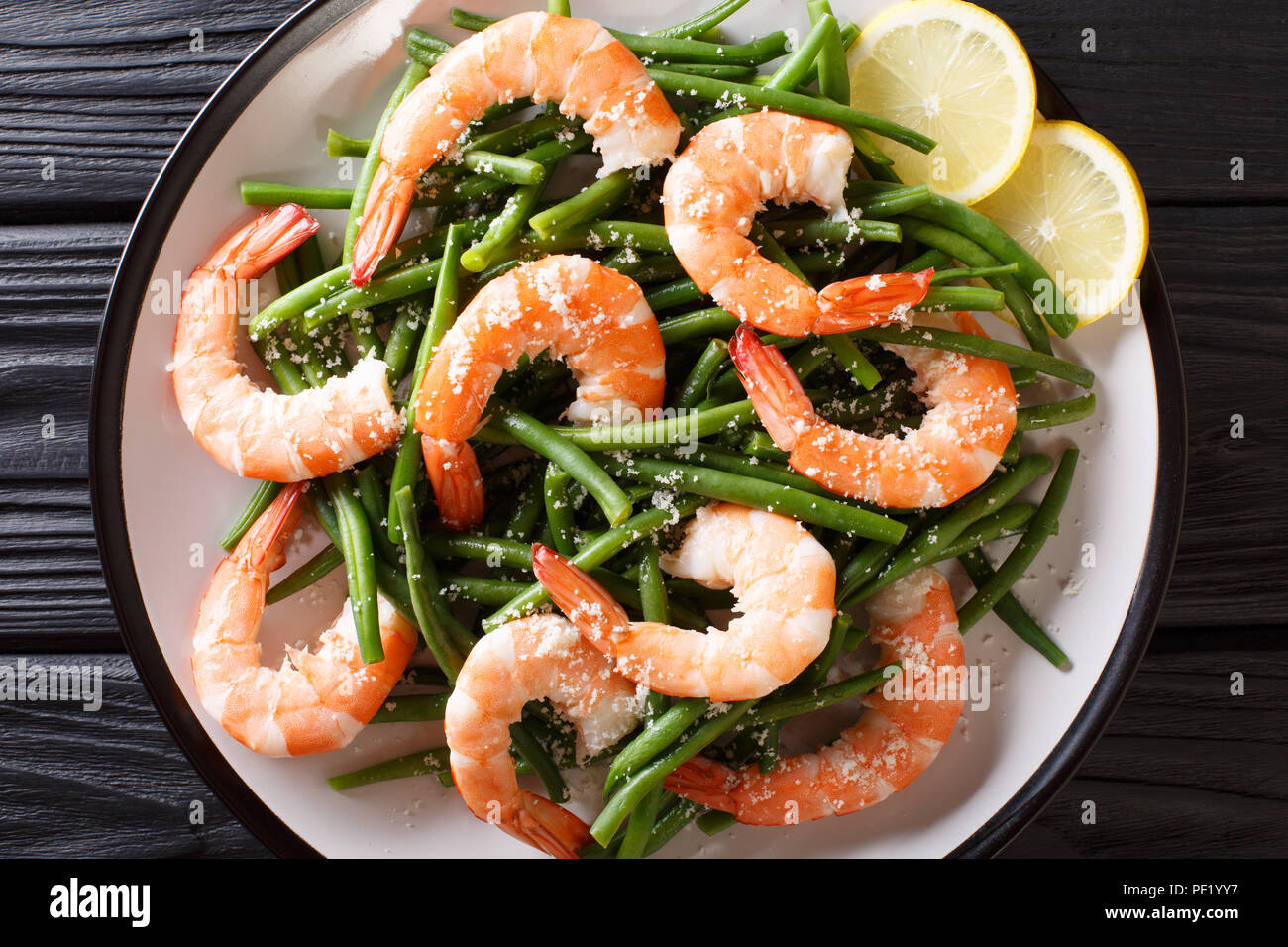 Stir fry prawns with green beans, cheese and lemon close-up on a plate on the table. horizontal top view from above - Stock Image
