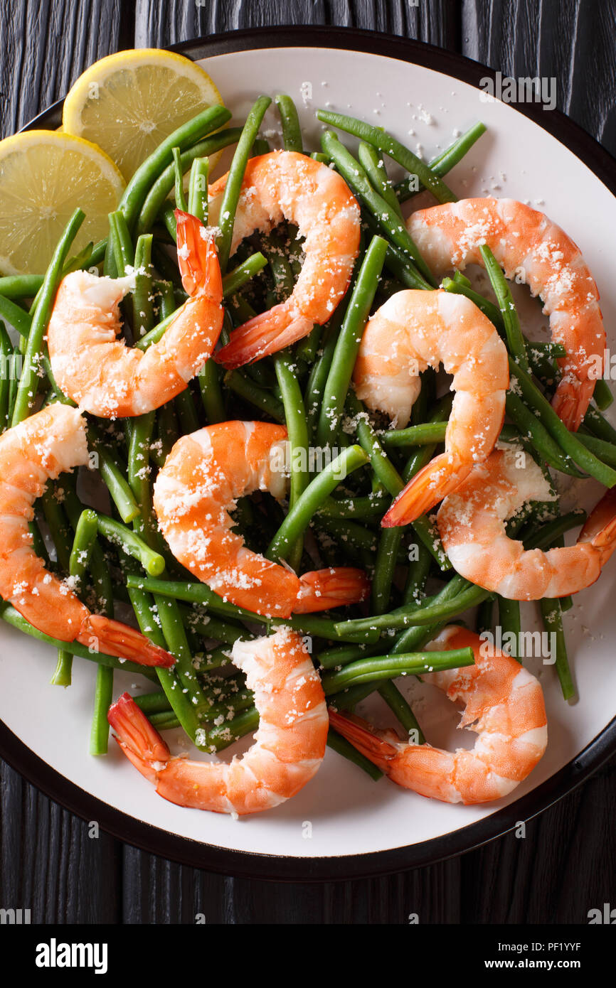 Stir fry prawns with green beans, cheese and lemon close-up on a plate on the table. Vertical top view from above - Stock Image