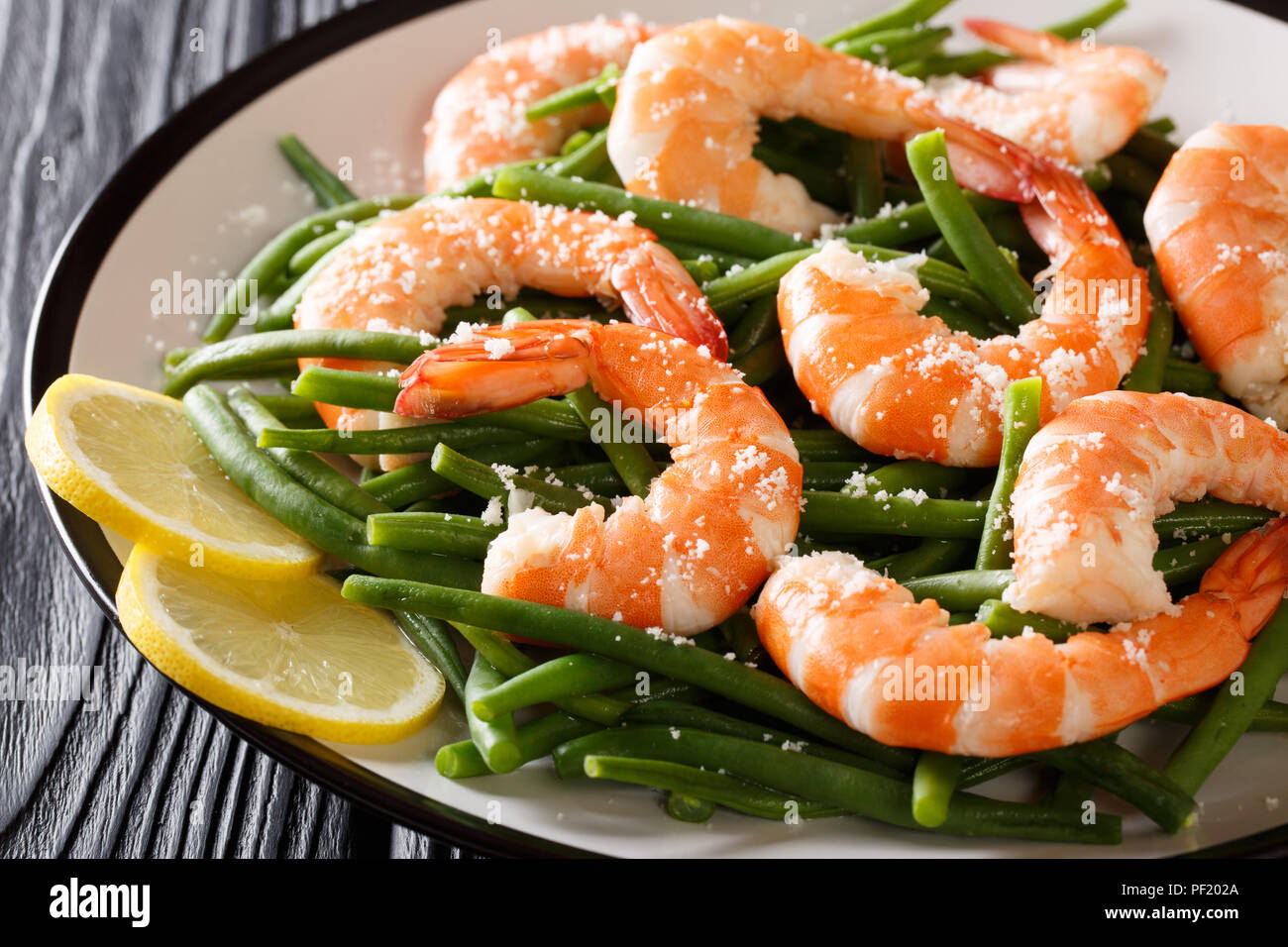 Stir fry prawns with green beans, cheese and lemon close-up on a plate on the table. horizontal - Stock Image