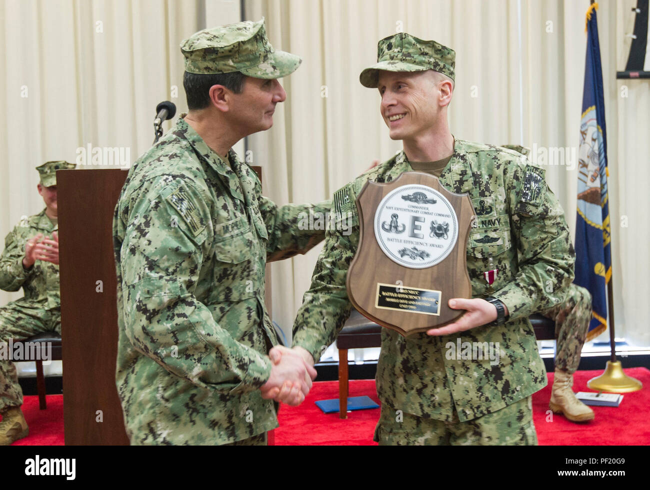 160219-N-SF508-134   VIRGINIA BEACH, Va. (Feb. 19, 2016) Rear Adm. Frank Morneau, Commander, Navy Expeditionary Combat Command, presents Cmdr. Jeffrey Morganthaler, commanding officer of Mobile Diving and Salvage Unit Two (MDSU 2) with the Battle Efficiency award during a change of command ceremony at Joint Expeditionary Base Little Creek. Cmdr. Morganthaler was relieved by Cmdr. William Wirtz as commanding officer of MDSU 2, the only east coast mobile diving and salvage unit. (U.S. Navy photo by Mass Communication Specialist 2nd Class Charles Oki/Released) - Stock Image