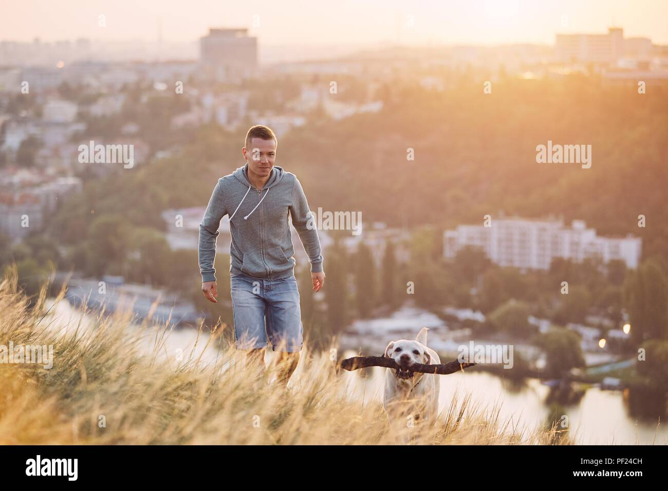 Morning walk with dog. Young man and his labrador retriever on the meadow against city at sunrise. - Stock Image
