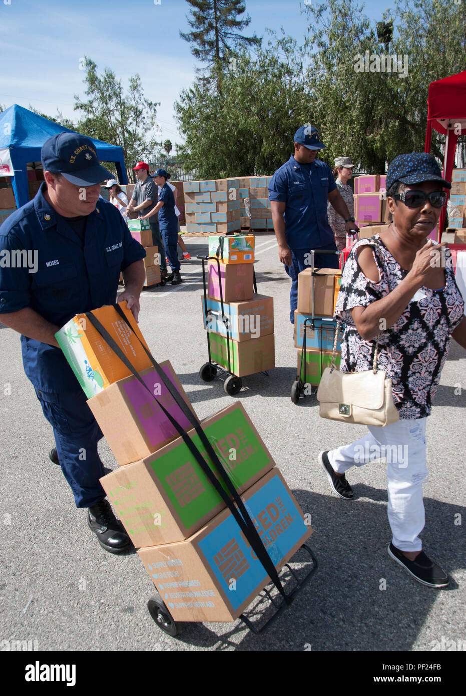 Coast Guard members from both Sector and Base Los Angeles/Long Beach worked together with members of the Air Force, Marine Corps and Army to support the 'Feed the Community' event with Feed the Children, Saturday, Oct. 24, 2015. This event took place at the Salvation Army Seimon Family Youth and Community center in Los Angeles. Military members worked along side Los Angeles Clippers players, staff, season ticket holders and military family members to distribute 1,200 boxes of food and personal care items to families in need. (U.S. Coast Guard photo by Petty Officer 1st Class Sondra-Kay Kneen) - Stock Image