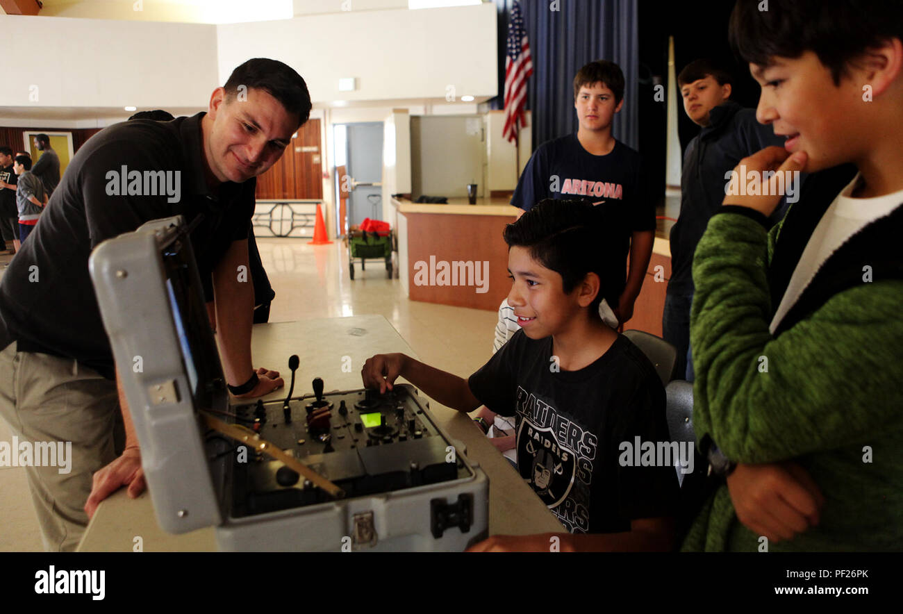 Staff Sgt. Edward Garcia, an Explosive Ordnance Disposal technician with 1st EOD Co., 7th Engineer Support Battalion, 1st Marine Logistics Group, supervises a James E. Potter Junior High School student attempting to drive the TALON EOD robot during a visit to the school in Fallbrook, Calif., Feb. 29, 2016. During the visit, EOD Marines explained the various capabilities of military robots and performed a practical application of EOD's bomb-detecting robots.  (U.S. Marine Corps photo by Sgt. Laura Gauna/released) - Stock Image