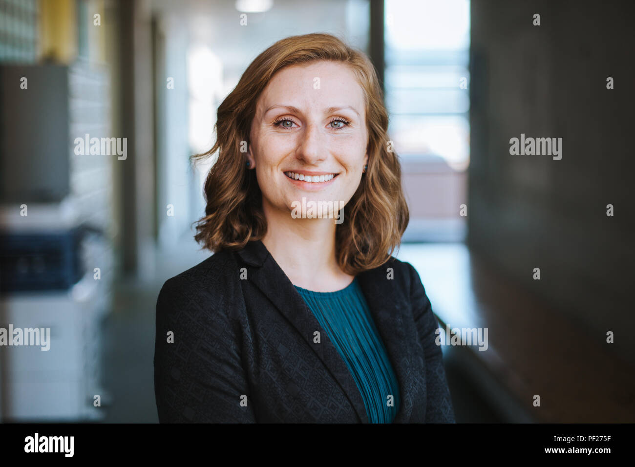 elegant and confident business woman smiles at the camera - Stock Image