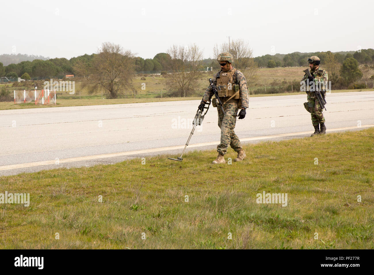 Sergeant Jose Cabrera, a squad leader with Special-Purpose Marine Air-Ground Task Force Crisis Response- Africa, sweeps the airfield for possible explosives alongside a Portuguese Marine during an airfield seizure exercise as part of Operation Real Thaw in Seia, Portugal, Feb. 22, 2016. Marines with SPMAGTF-CR-AF are continuously conducting bilateral training with partner nations to sustain and improve core mission essential tasks and build interoperability to prepare for real world operations on the African continent. (U.S. Marine Corps photo by Sgt. Tia Nagle) - Stock Image