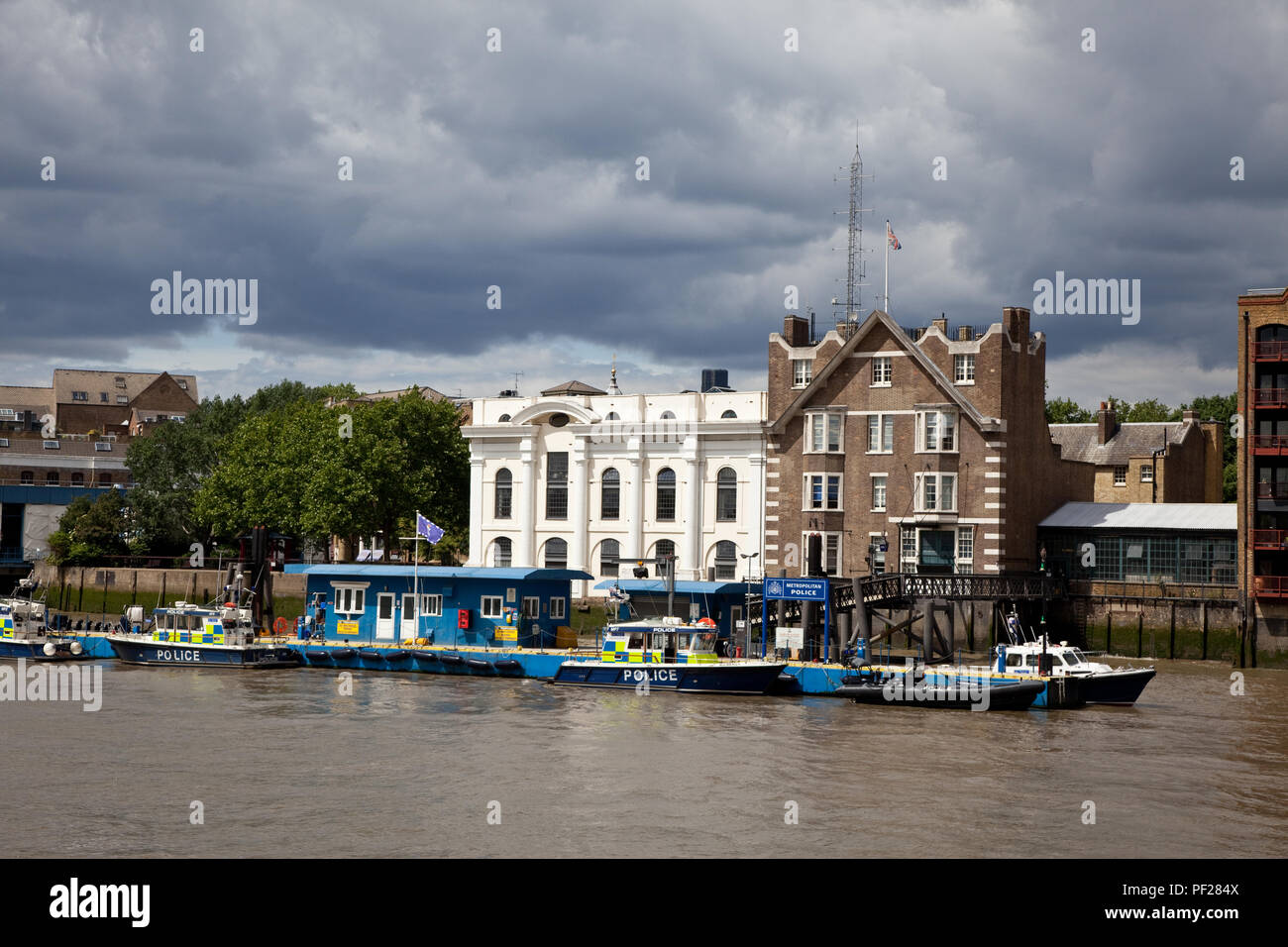 Metropolitan Police Marine Policing Unit, Wapping, London, from the River Thames with moody sky - Stock Image