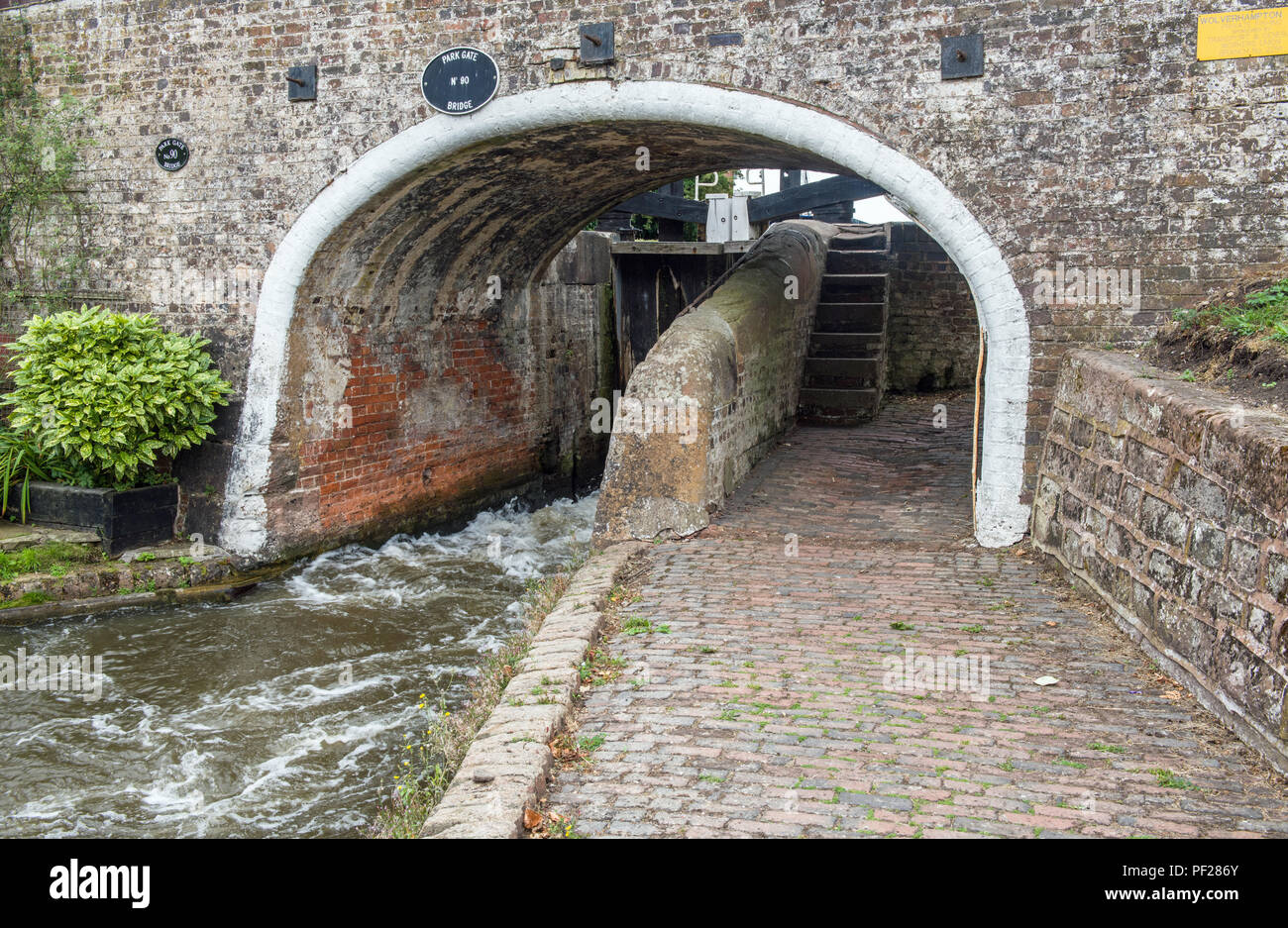 The Staffordshire and Worcestershire Canal near Penkridge showing water coming out between the opening lock gates above. Stock Photo