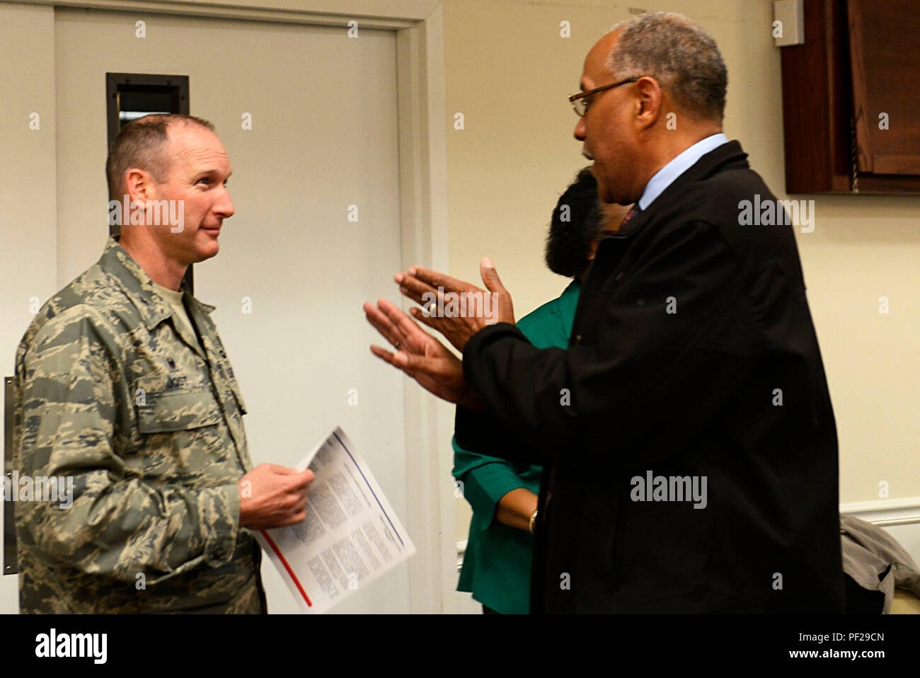 U.S. Air Force Col. Stephen Jost, 20th Fighter Wing commander, talks with South Carolina State Guard Col. William Oden, Retirees on Call Shaw coordinator, during a deployed family dinner at Shaw Air Force Base, S.C., Feb. 22, 2016. Team Shaw leadership attended the event and showed their support for deployed members by conversing with their families and program sponsors. (U.S. Air Force photo by Airman 1st Class Christopher Maldonado) - Stock Image
