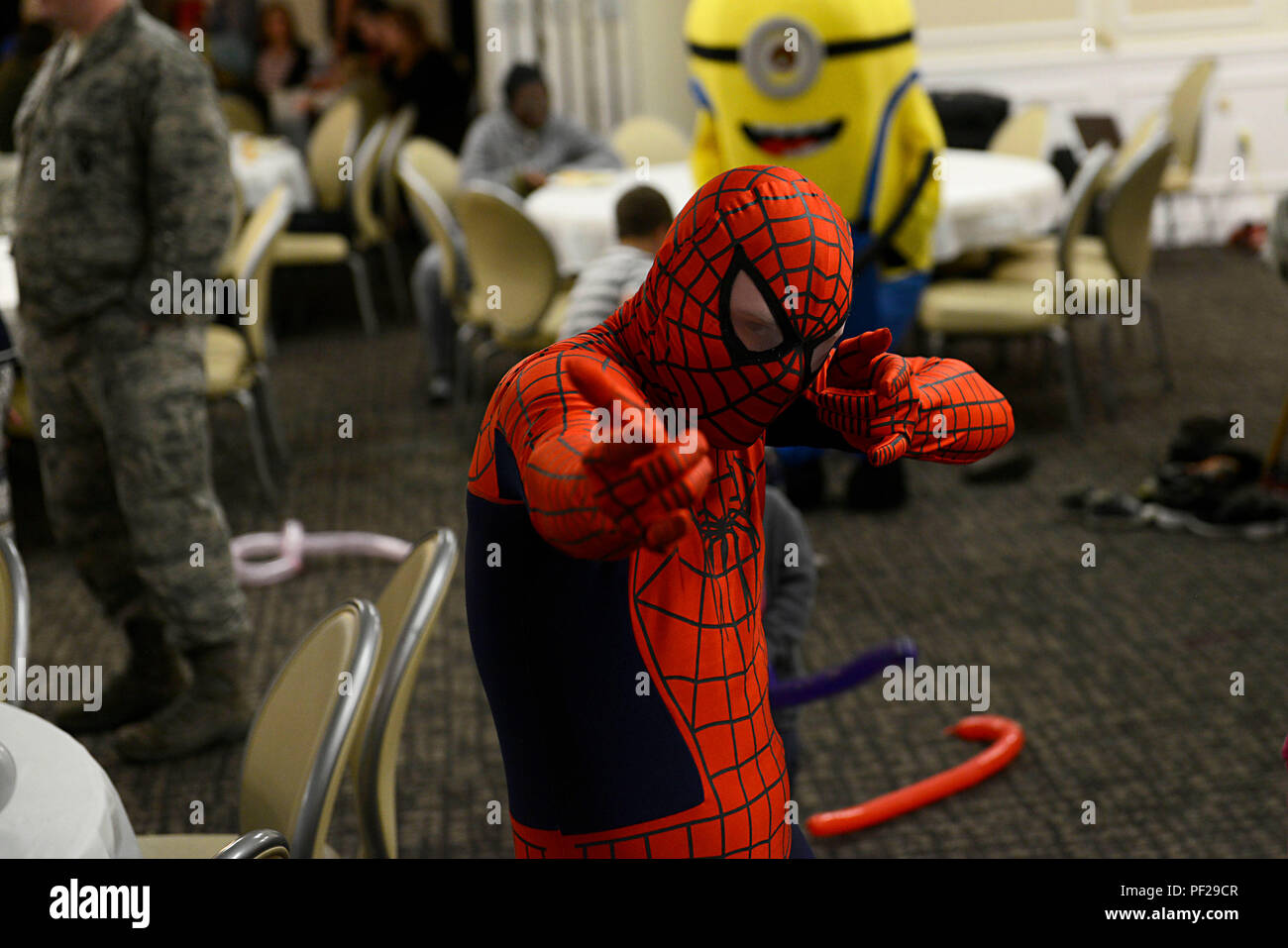 A volunteer dressed as Spiderman poses for a photo during a deployed family dinner at Shaw Air Force Base, S.C., Feb. 22, 2016. Children of deployed service members were given the opportunity to do various activities including: playing with cartoon characters, playing in a bounce house, face painting, and balloon sword fights. (U.S. Air Force photo by Airman 1st Class Christopher Maldonado) - Stock Image