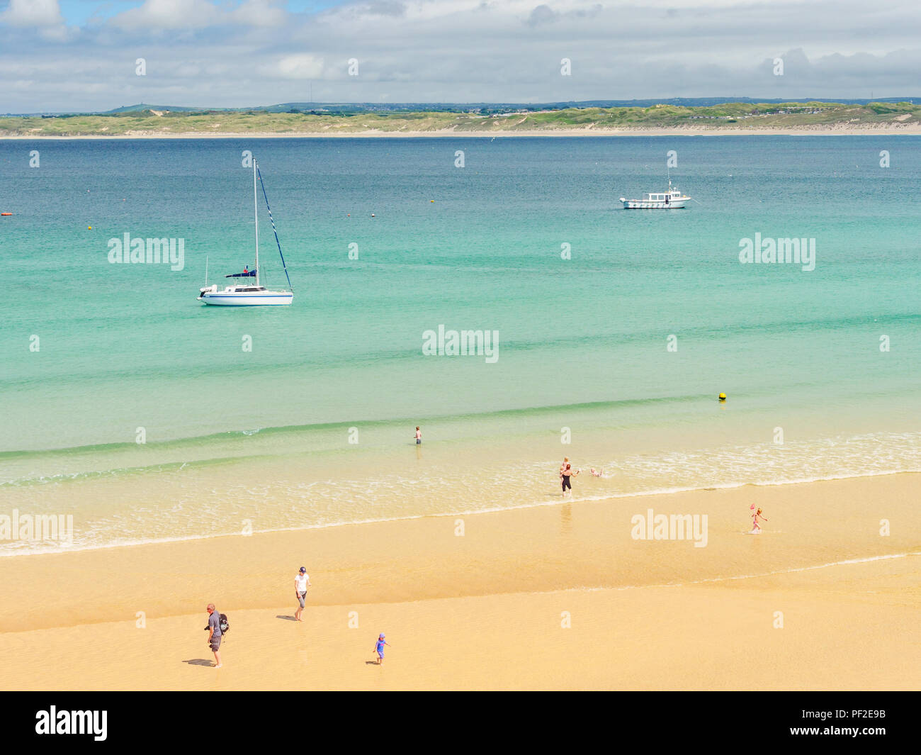 ST IVES, ENGLAND - JUNE 19: Families enjoying paddling in the sea at Porthminster Beach, in St Ives, on a hot Summer day. In St Ives, Cornwall, Englan - Stock Image