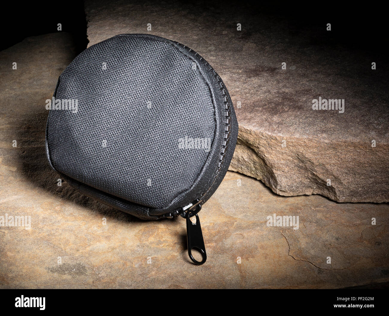 Zippered black tactical pouch on a pair of rocks - Stock Image