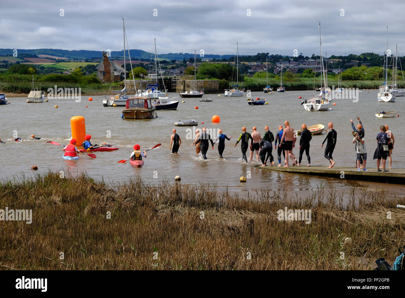 Topsham, Devon, UK. Swimmers take part in the annual Topsham to Turf Ferry swim along the River Exe in Topsham - Stock Image