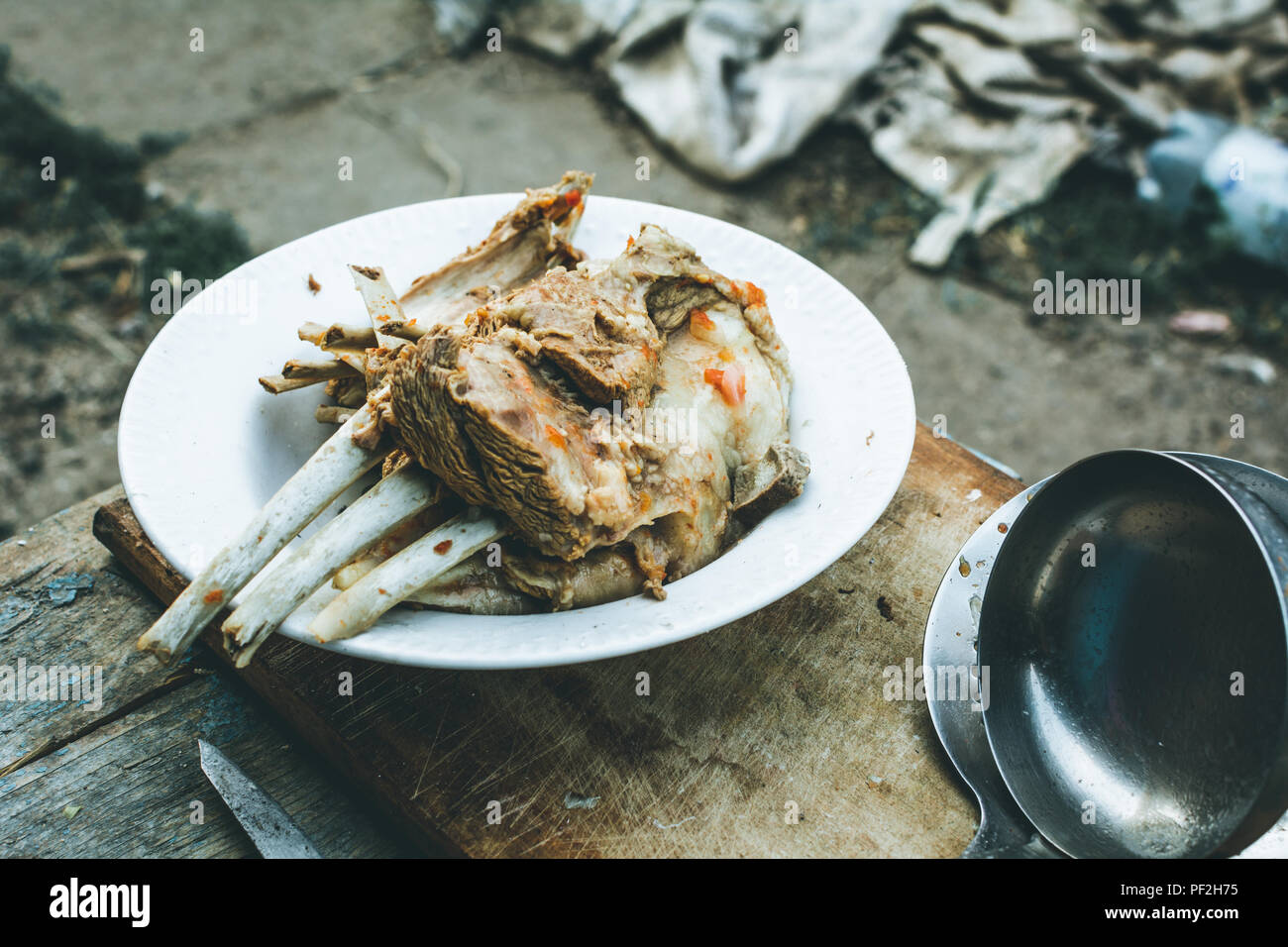 Boiled lamb in a plate on a wooden board - Stock Image
