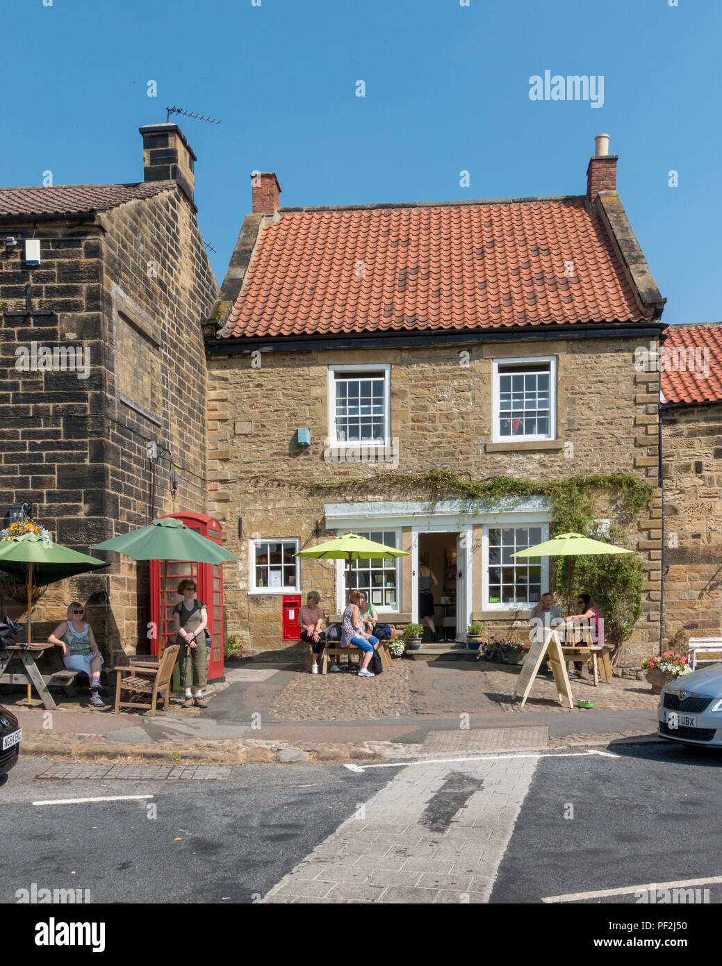 People sit outside the cafe 'Osmotherley Tea and Coffee Shop' North Yorkshire Moors in hot weather - Stock Image