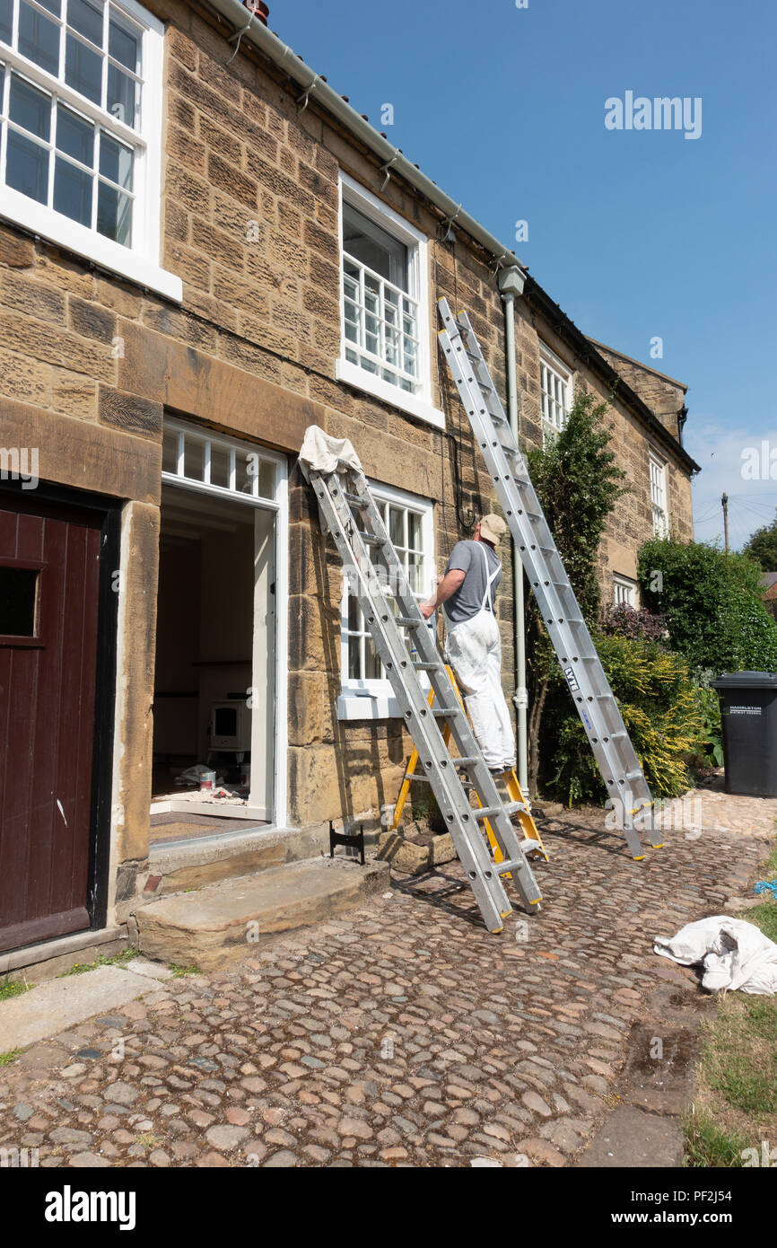 Painter and decorator painting sash windows on a ladder in the North Yorkshire village of Osmotherley - Stock Image