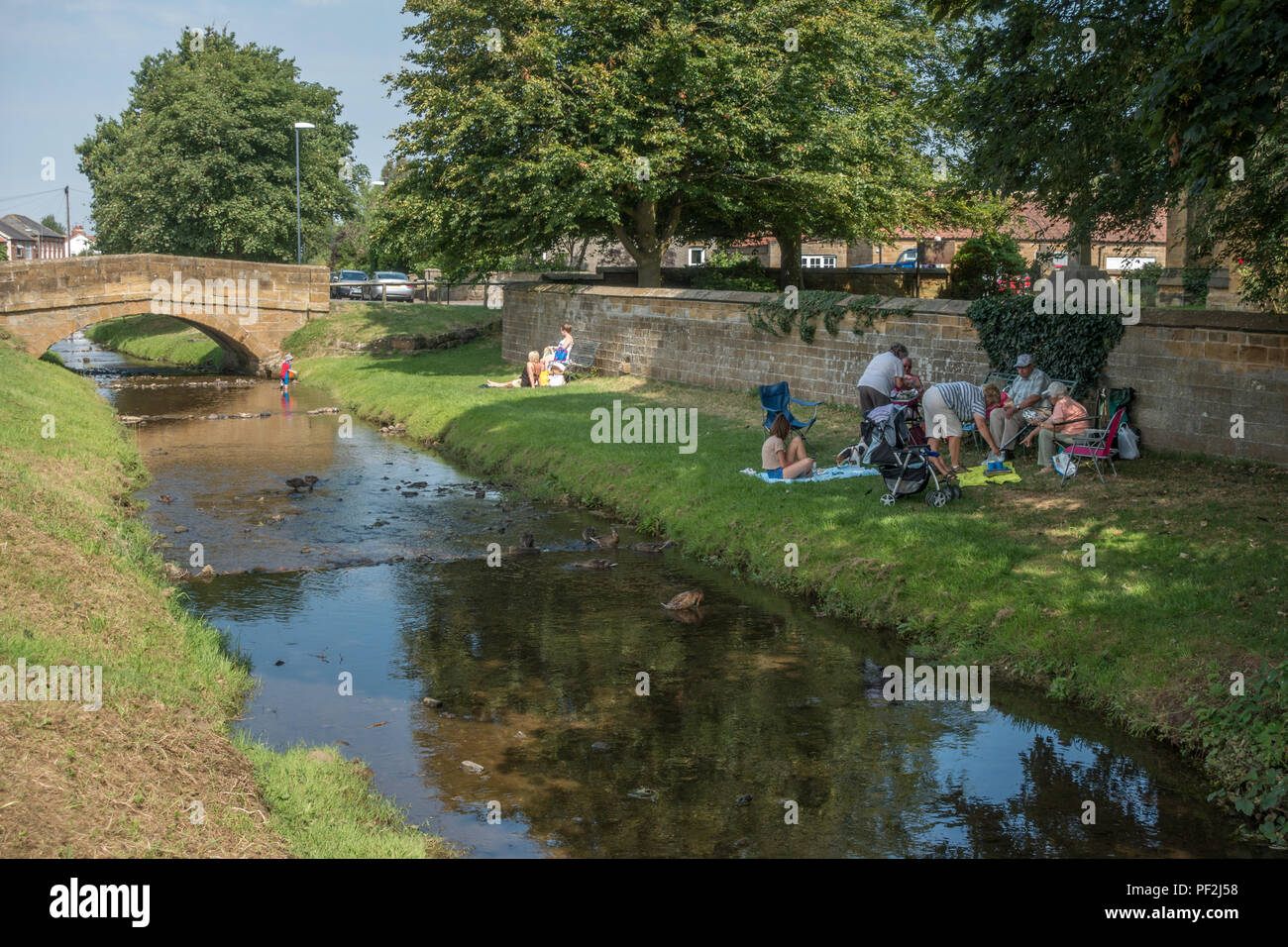 Whole families enjoy picnics in shady places, Crook Beck in Swainby, North Yorkshire Moors - Stock Image