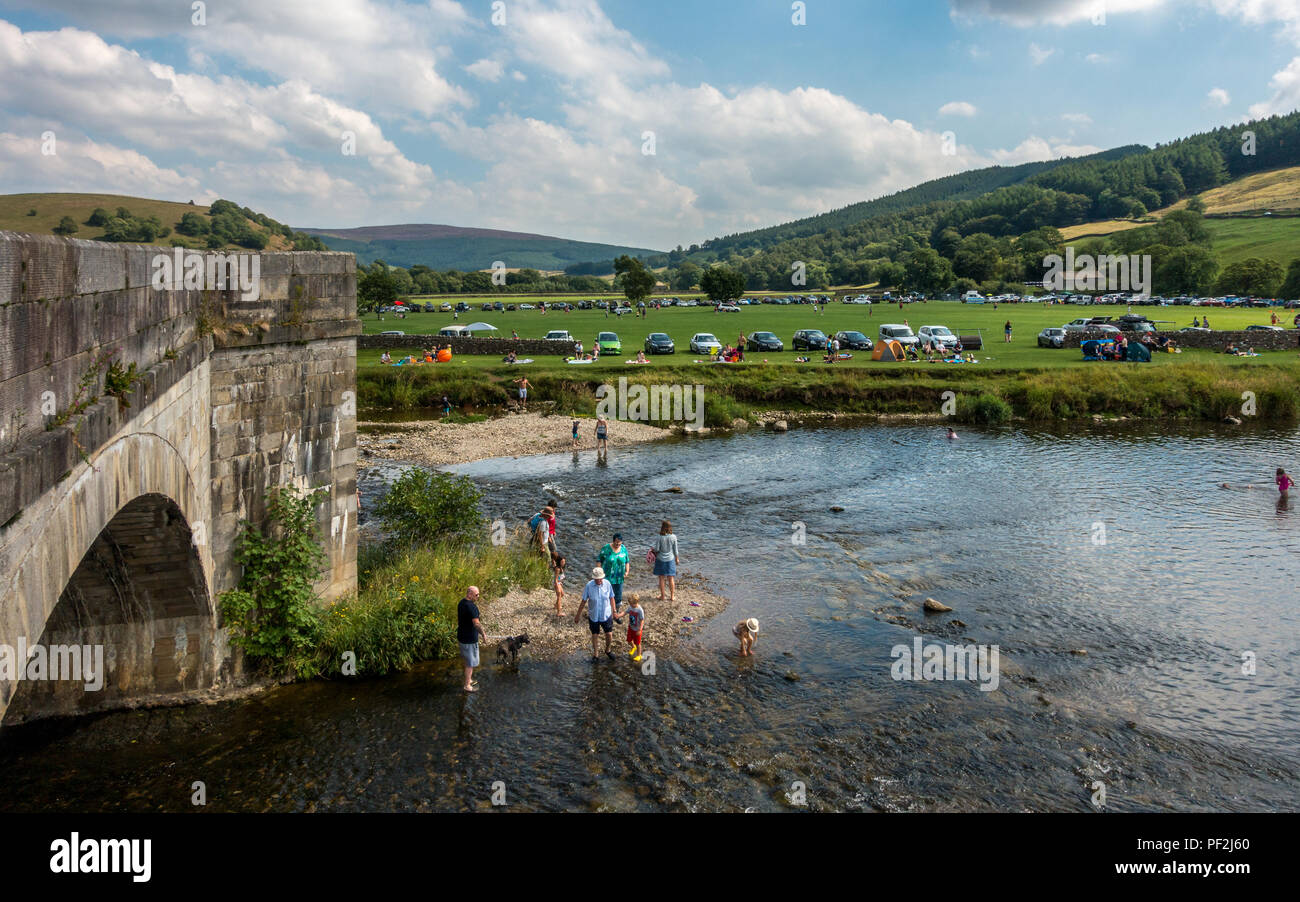 Costa del Burnsall: Pretty riverside village, Burnsall, becomes a tourist hotspot for locals wanting to cool off and enjoy a seaside feel without the  - Stock Image