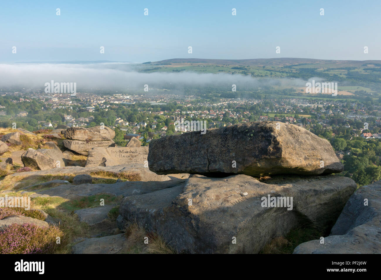 Ilkley town viewed from the Cow and Calf Rocks on Ilkley Moor in hot weather as the early mist burns off - Stock Image