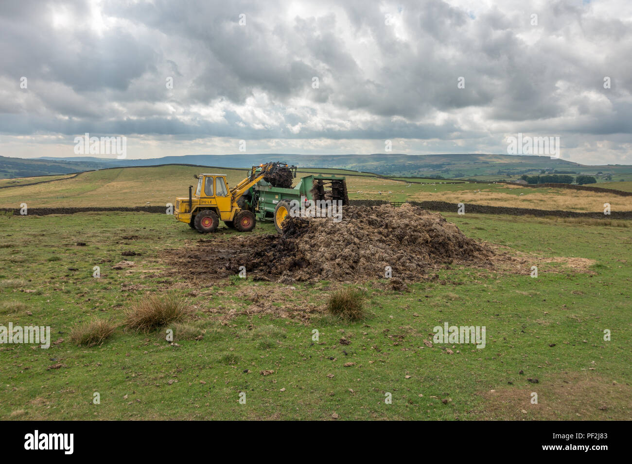 UK Farming: Farmer loading up a muck spreading vehicle - Stock Image
