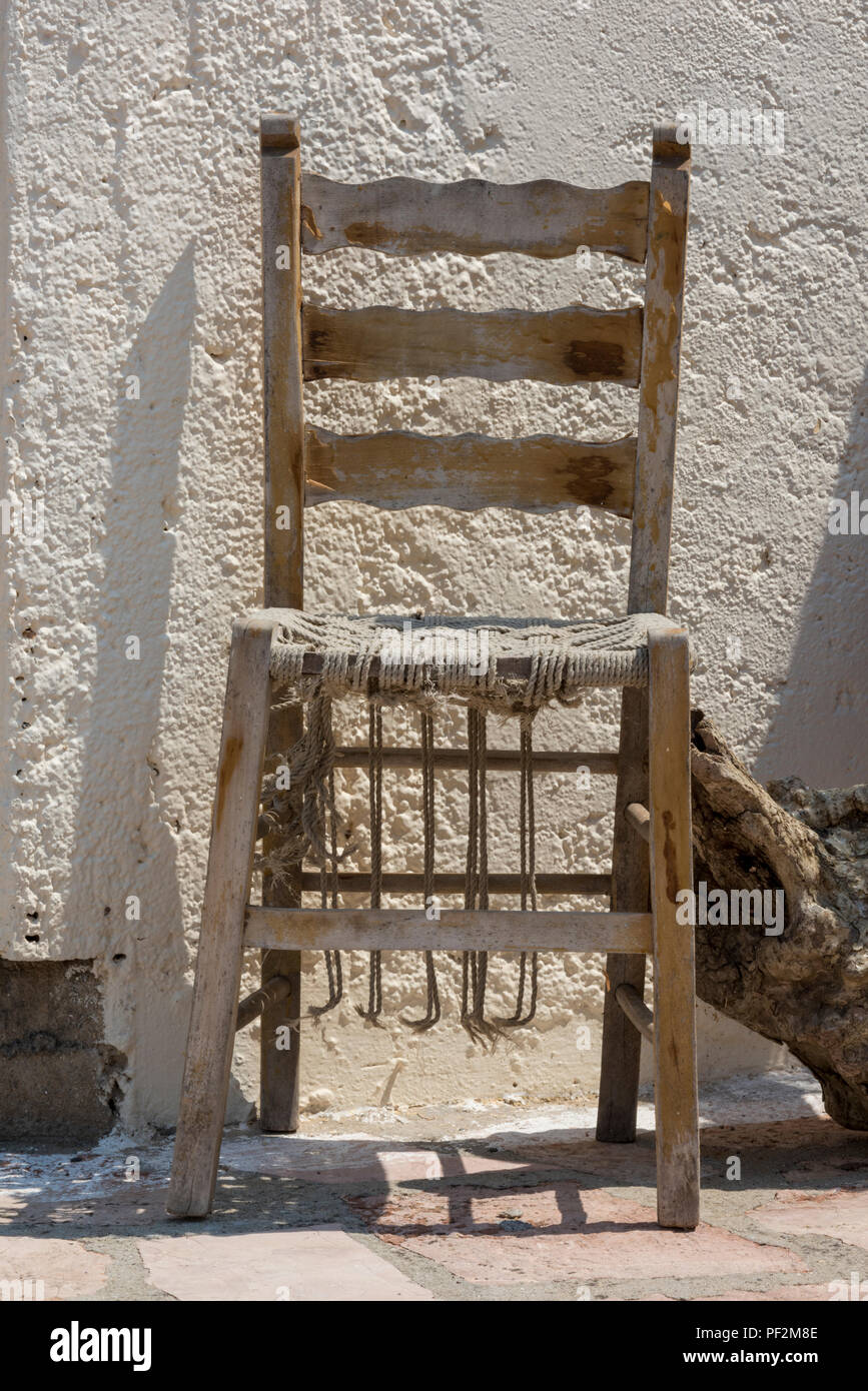 a rickety old worn out antique chair with a wicker seat. Stock Photo