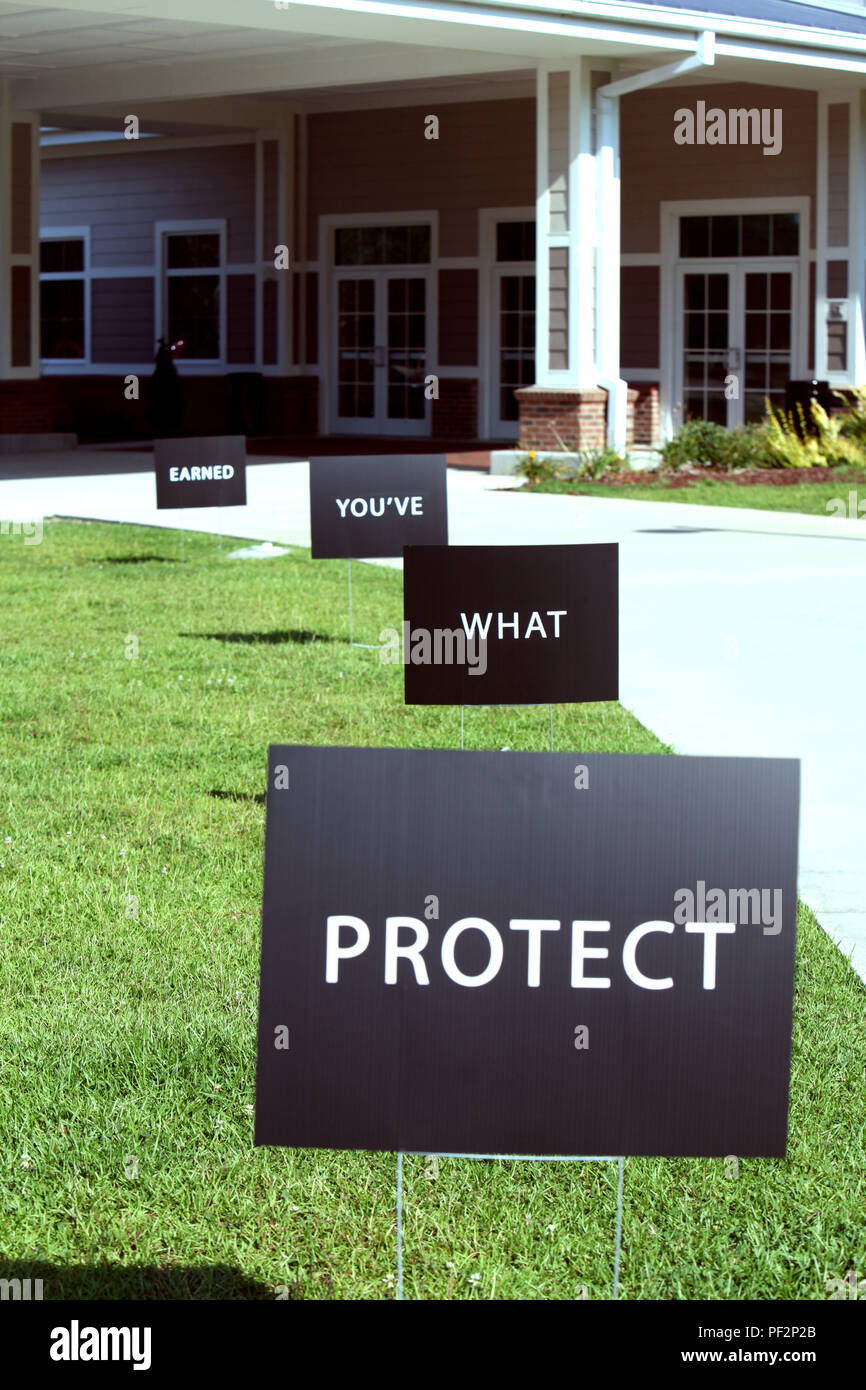 """Protect What You've Earned Campaign signs line a sidewalk during a """"Protect What You've Earned"""" brief at Marine Corps Air Station Cherry Point, N.C., Aug. 18, 2015. The campaign promotes the development of peer support systems and responsible decision-making and actions. It was designed to decrease alcohol-related incidents and all destructive behaviors that decrease readiness and have a negative impact on the Marines, Sailors, their families and the community. (U.S. Marine Corps photo by Pfc. Nicholas P. Baird/Released) - Stock Image"""