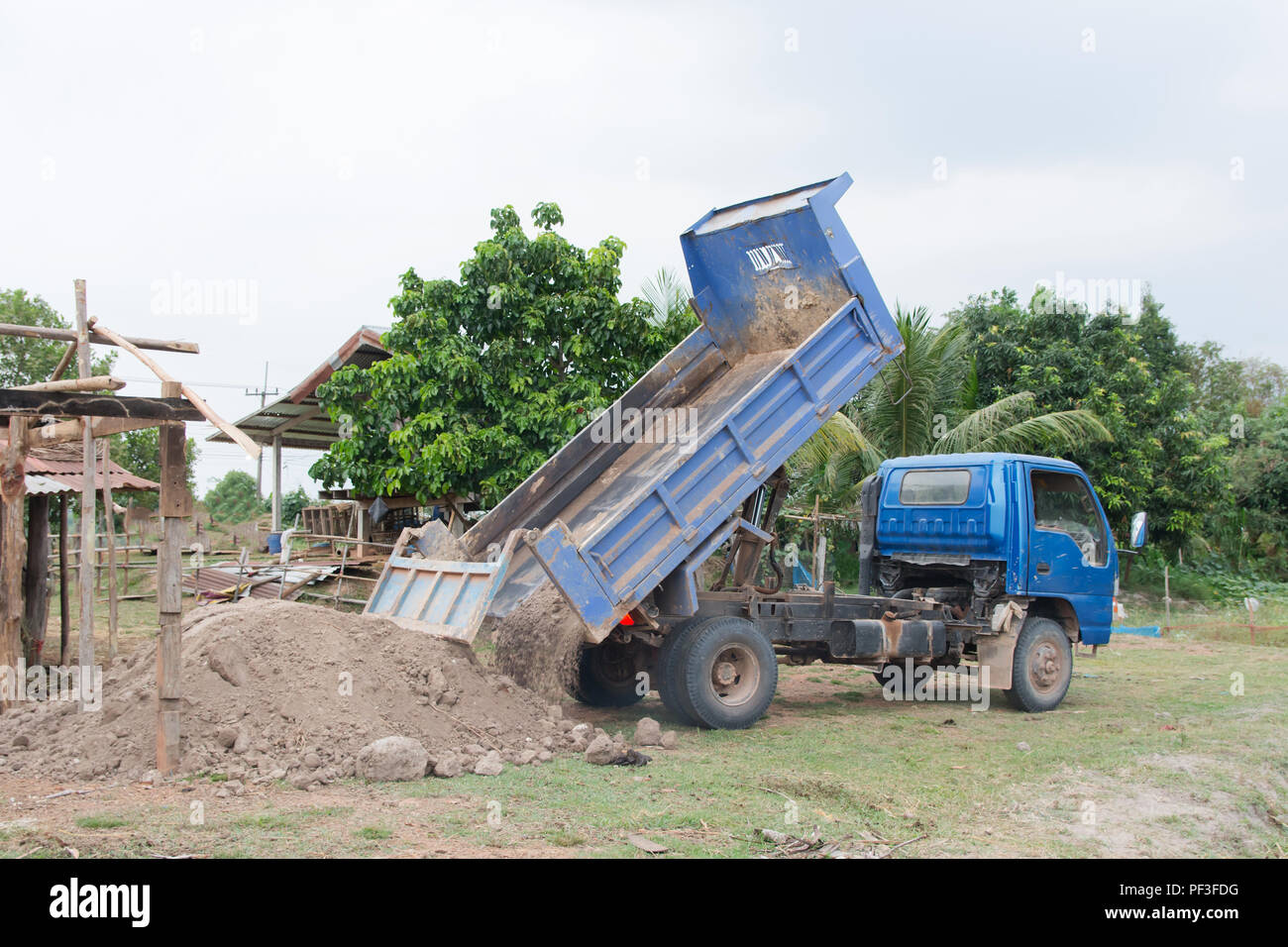 Blue dump truck unloading soil at construction site - Stock Image