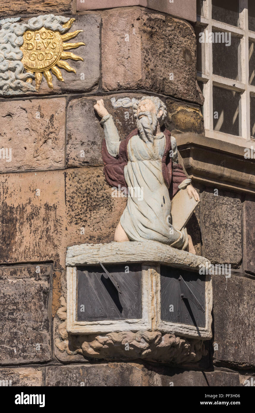 Edinburgh, Scotland, UK - June 13, 2012: Sundial on facade of John Knox House, a protestant reformer. Bearded Man looking up at golden sun, named God. - Stock Image