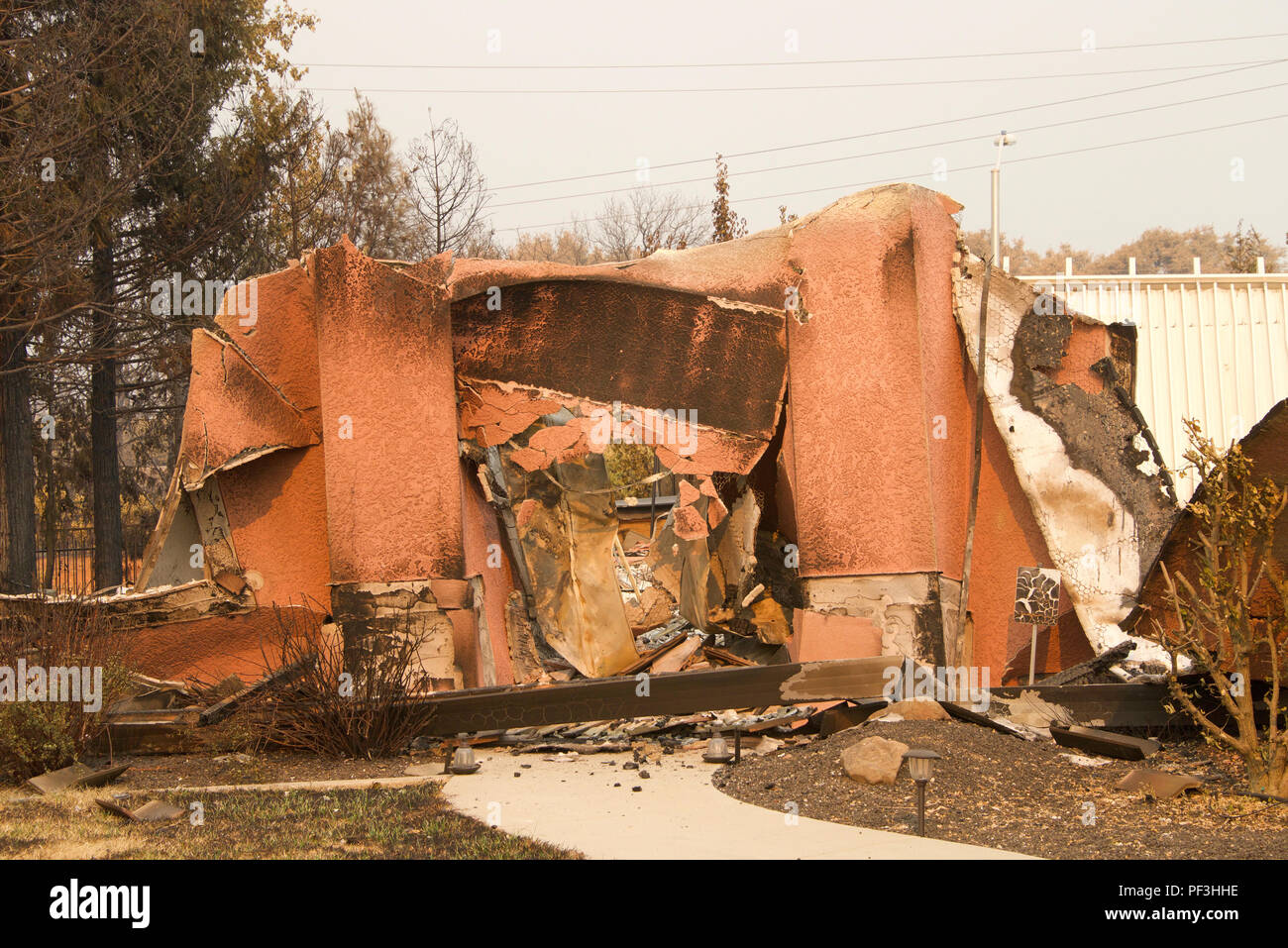 home severely burned with walls leaning and stucco hanging in the recent wild fire fire storm in Redding, California. Smoke and ash in the air as the  - Stock Image